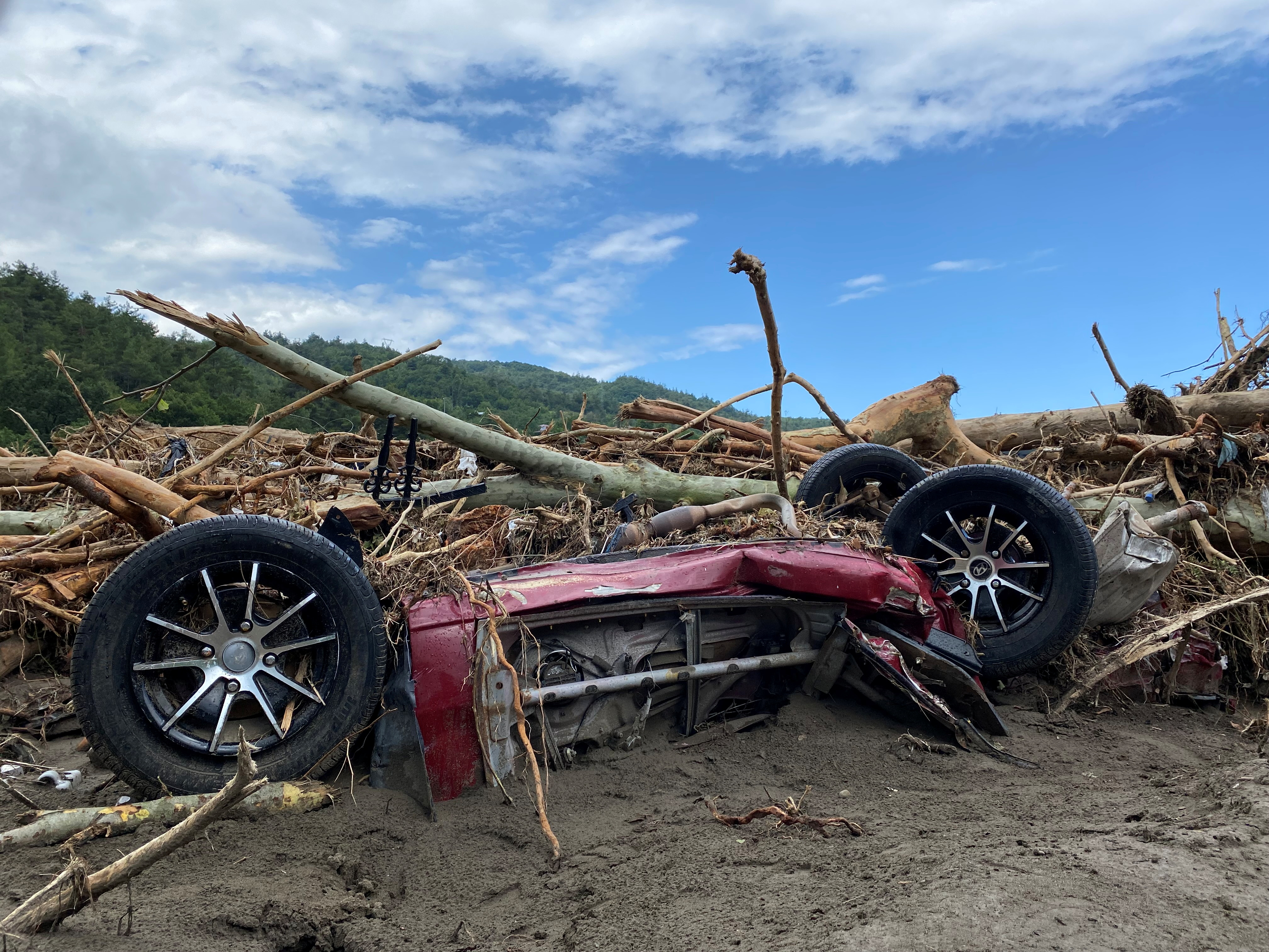 The wreckage of a vehicle is seen amid debris after flash floods swept through towns in the Turkish Black Sea region, in the town of Bozkurt, in Kastamonu province, Turkey, August 14, 2021. REUTERS/Bulent Usta