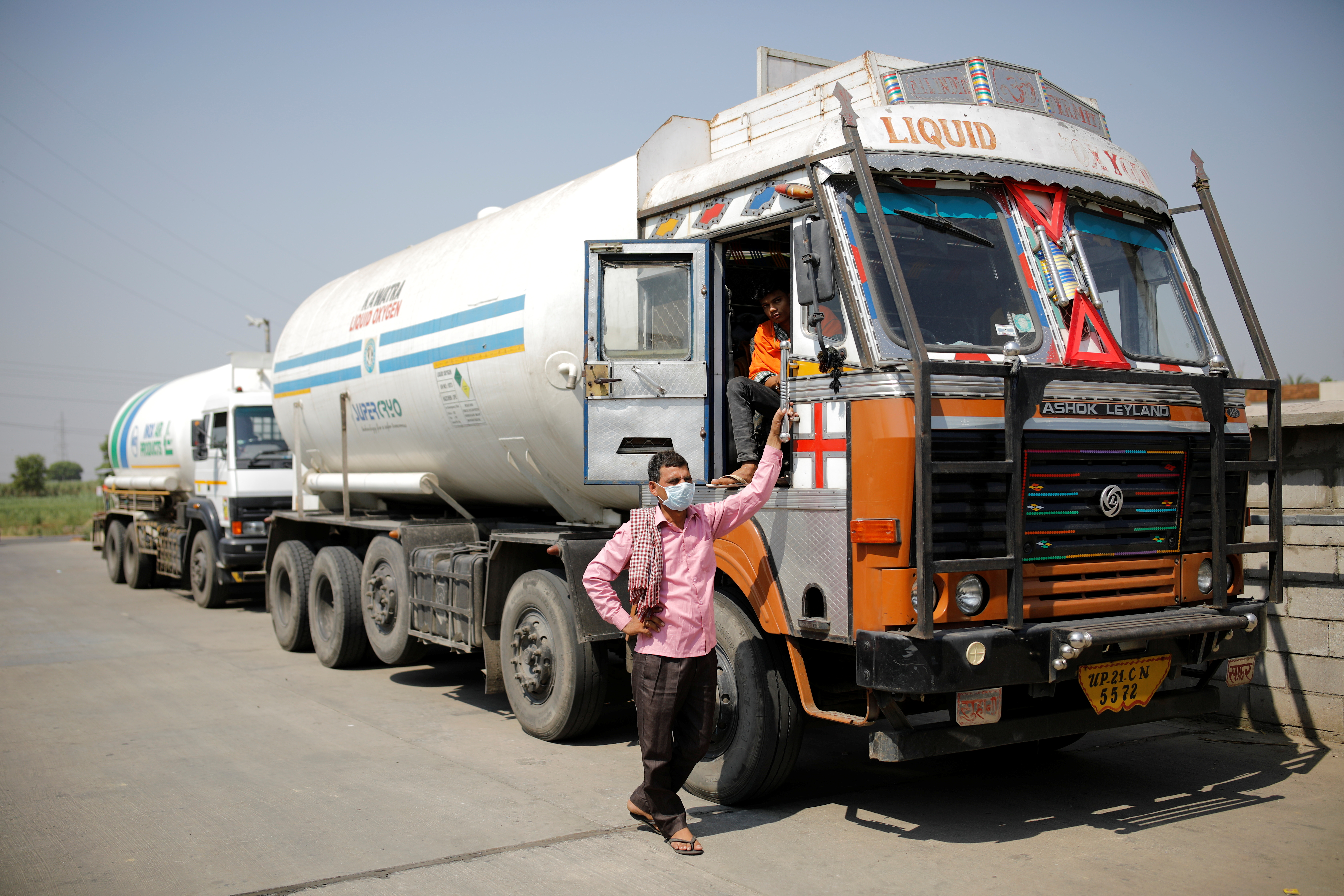 A driver stands next to an empty tanker as he waits for his turn to fill liquid oxygen, to be transported to a COVID-19 hospital, amidst the spread of the coronavirus disease, in Ghaziabad, on the outskirts of New Delhi, India, April 22, 2021. REUTERS/Adnan Abidi