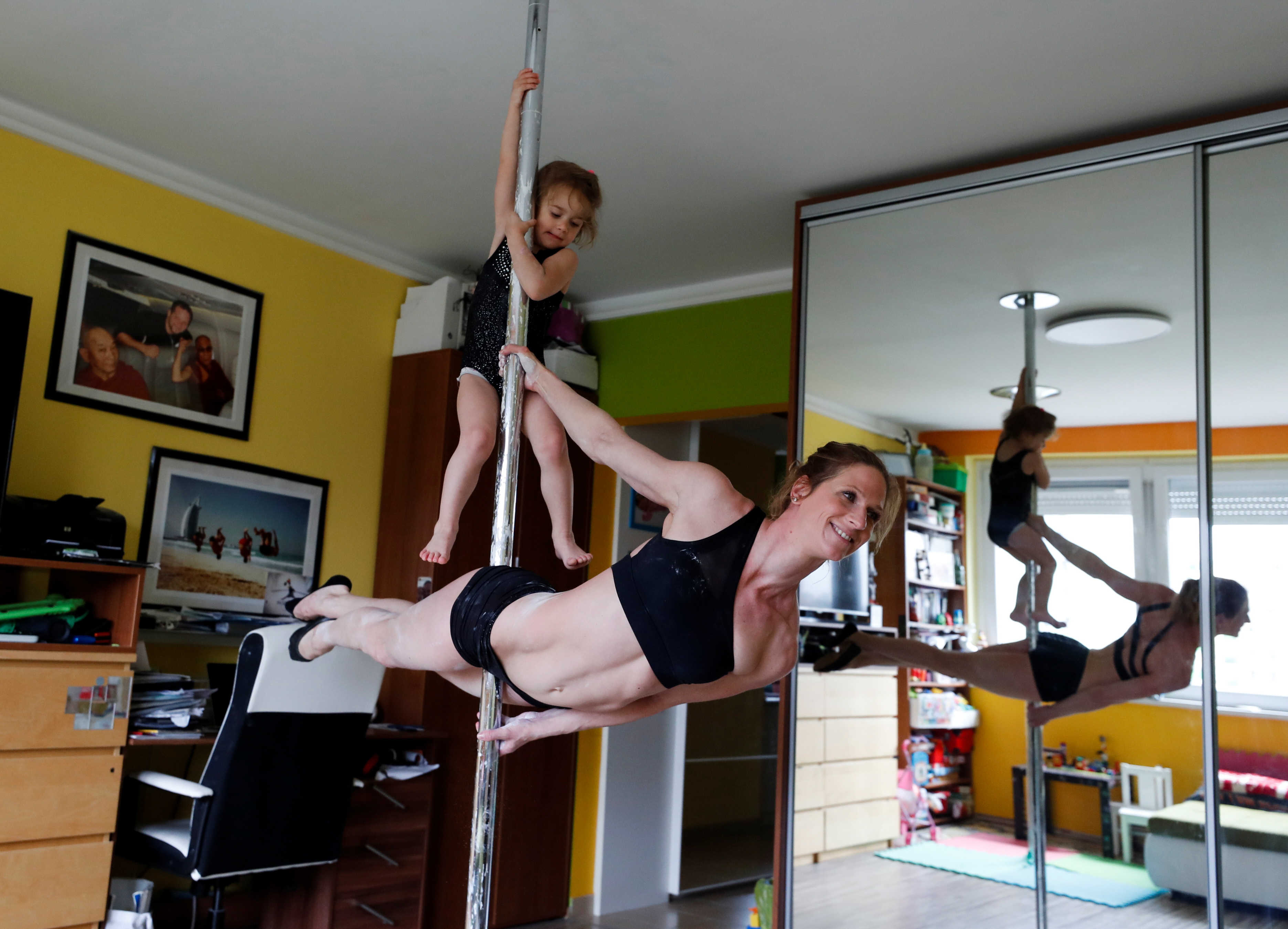 Pole acrobat, Kata Ott-Balogh, member of the Taurin Circus Group practices at home as her daughter Tetisz plays on the pole, amid the coronavirus disease (COVID-19) pandemic, in Budapest, Hungary, April 20, 2021. Picture taken April 20, 2021. REUTERS/Bernadett Szabo