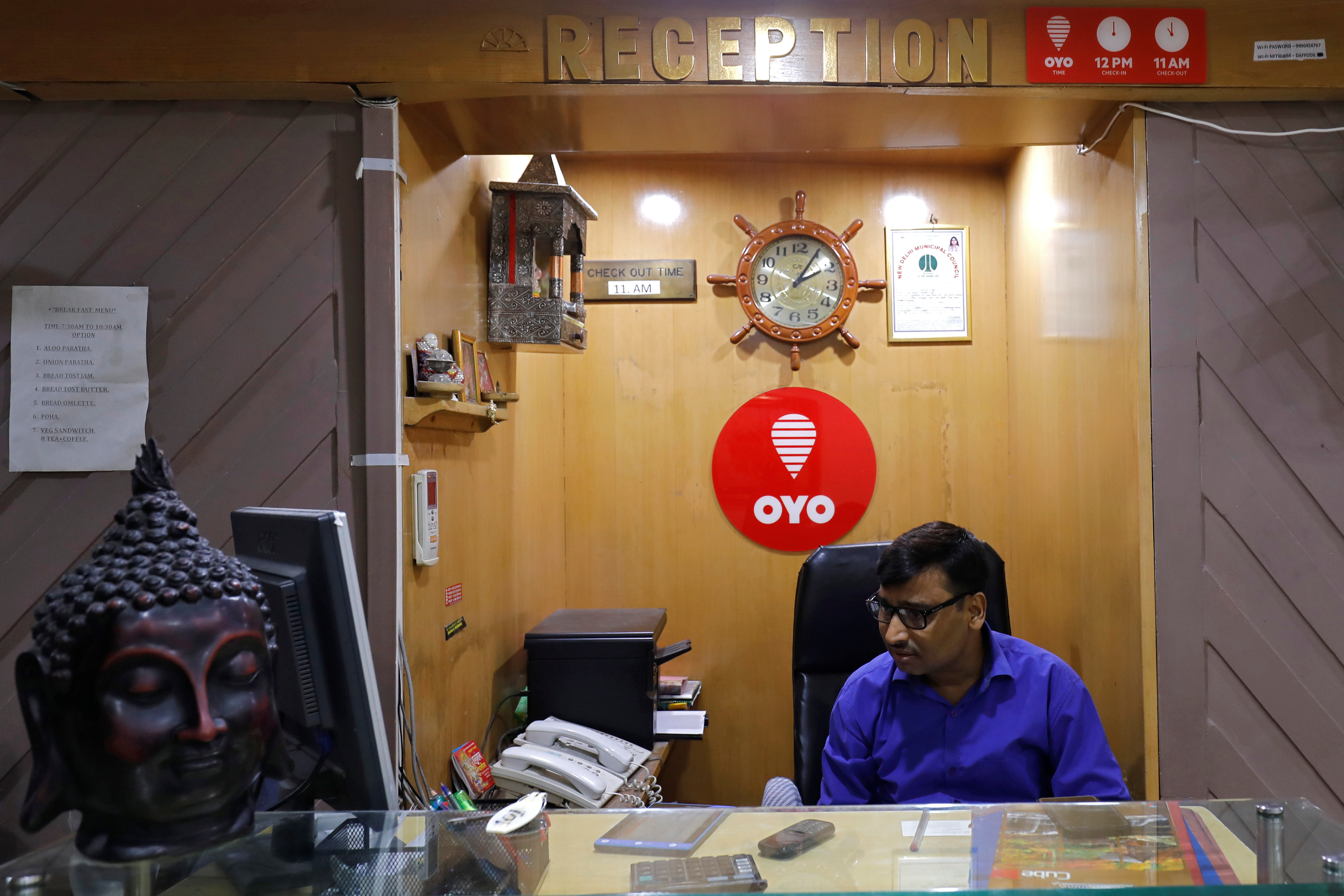 An employee sits next to the logo of OYO, India's largest and fastest-growing hotel chain, at the reception of a hotel in New Delhi, India, September 25, 2018. REUTERS/Anushree Fadnavis