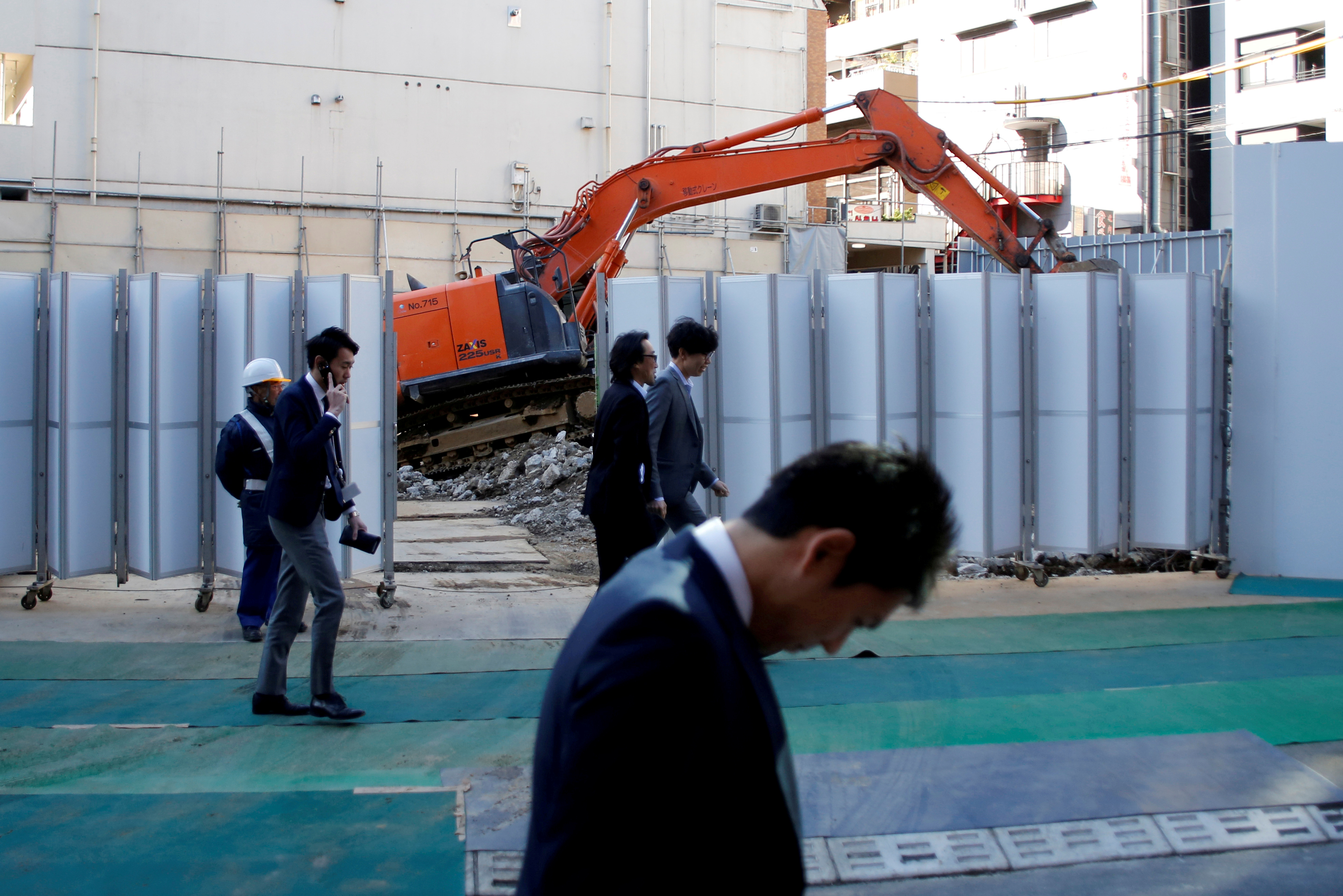 Businessmen walk past heavy machinery at a construction site in Tokyo's business district, Japan, January 16, 2017.    REUTERS/Toru Hanai/File Photo