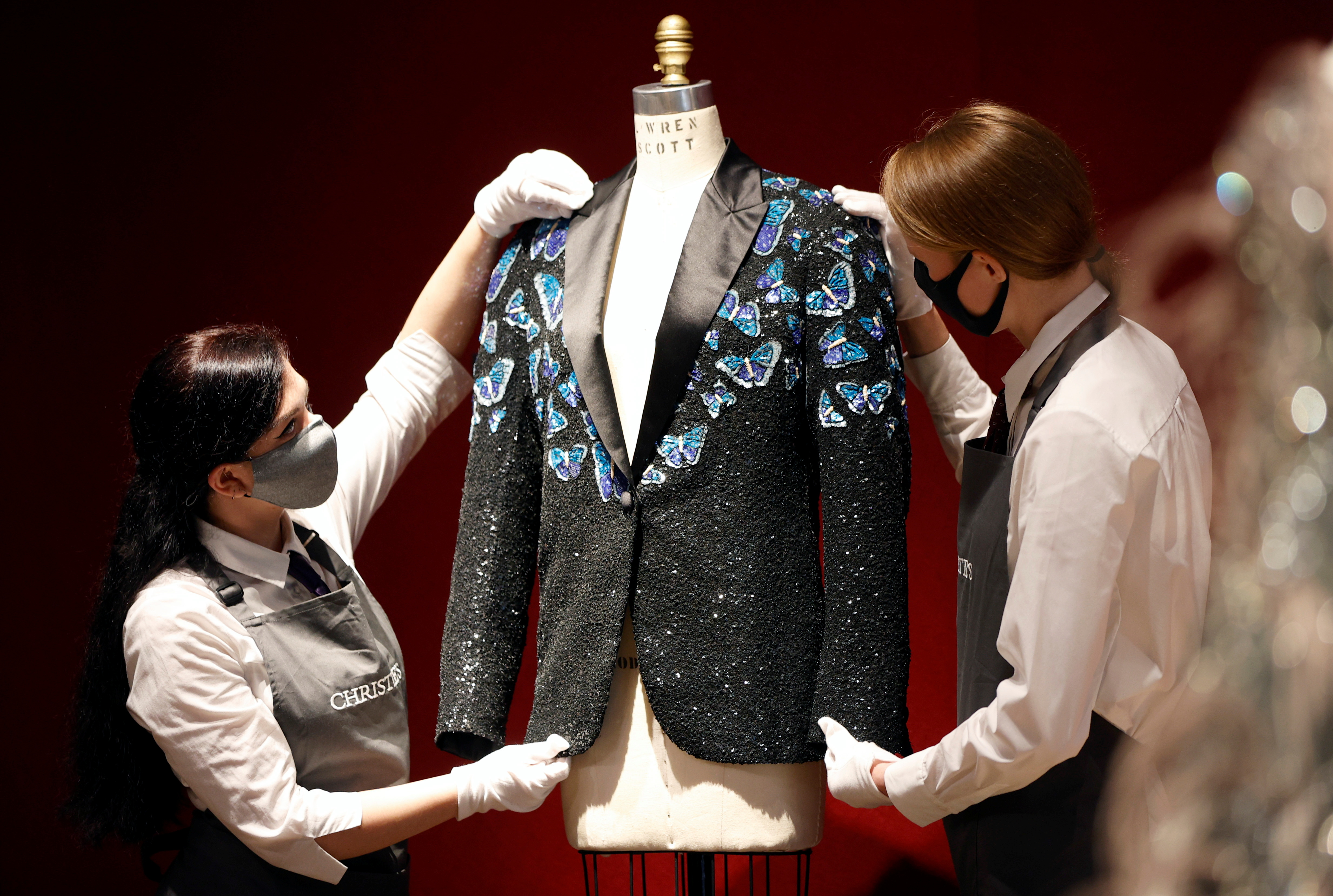 Gallery assistants pose for a photograph with the Butterfly jacket designed for Mick Jagger by designer L'Wren Scott at Christie's in London, Britain, June 10, 2021. REUTERS/John Sibley