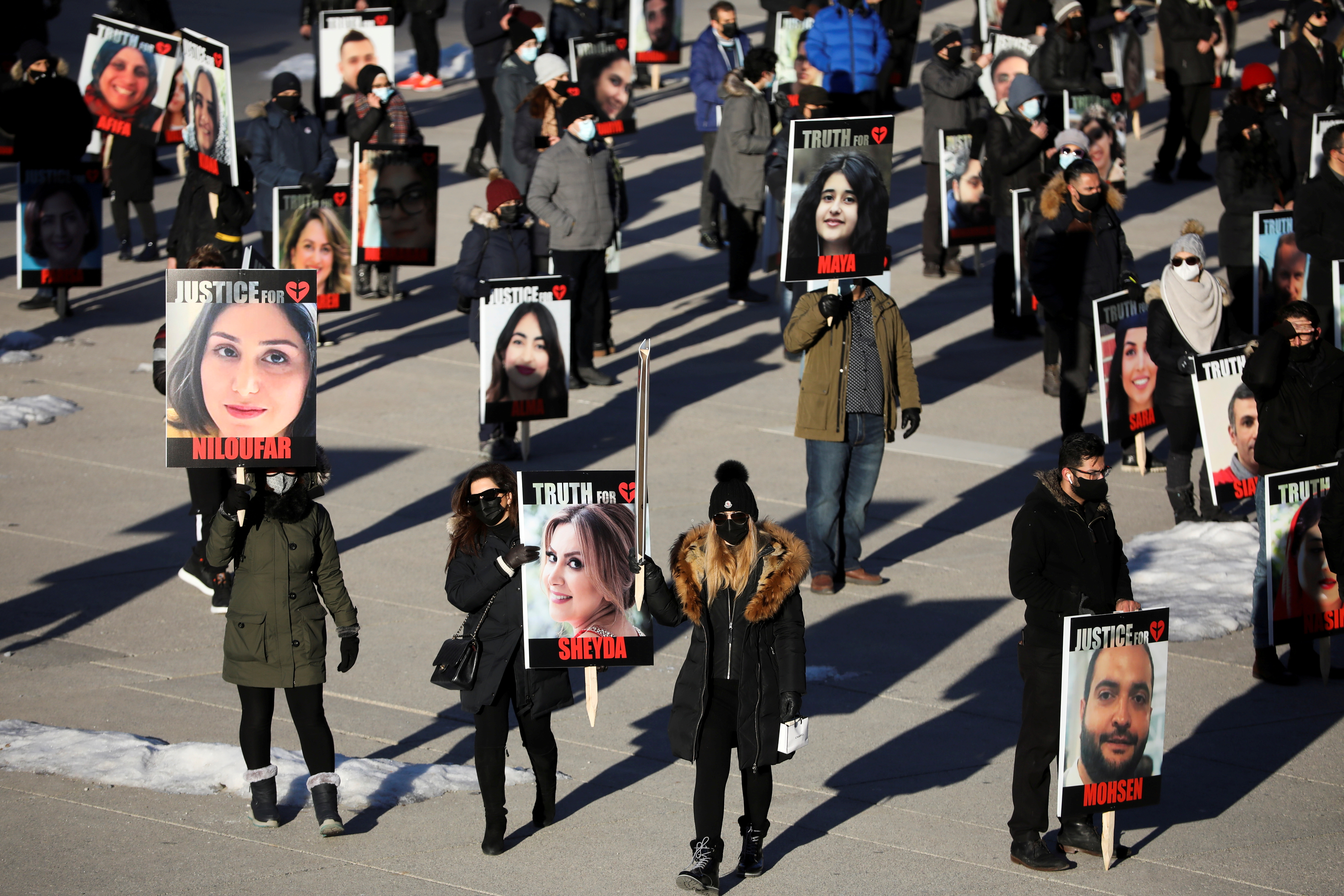 People hold placards with images of the victims of the downing of Ukraine International Airlines flight PS752, which was shot down near Tehran by Iran's Revolutionary Guards, as they gather to take part in a march to mark its first anniversary, in Toronto, Ontario, Canada January 8, 2021. REUTERS/Carlos Osorio/File Photo