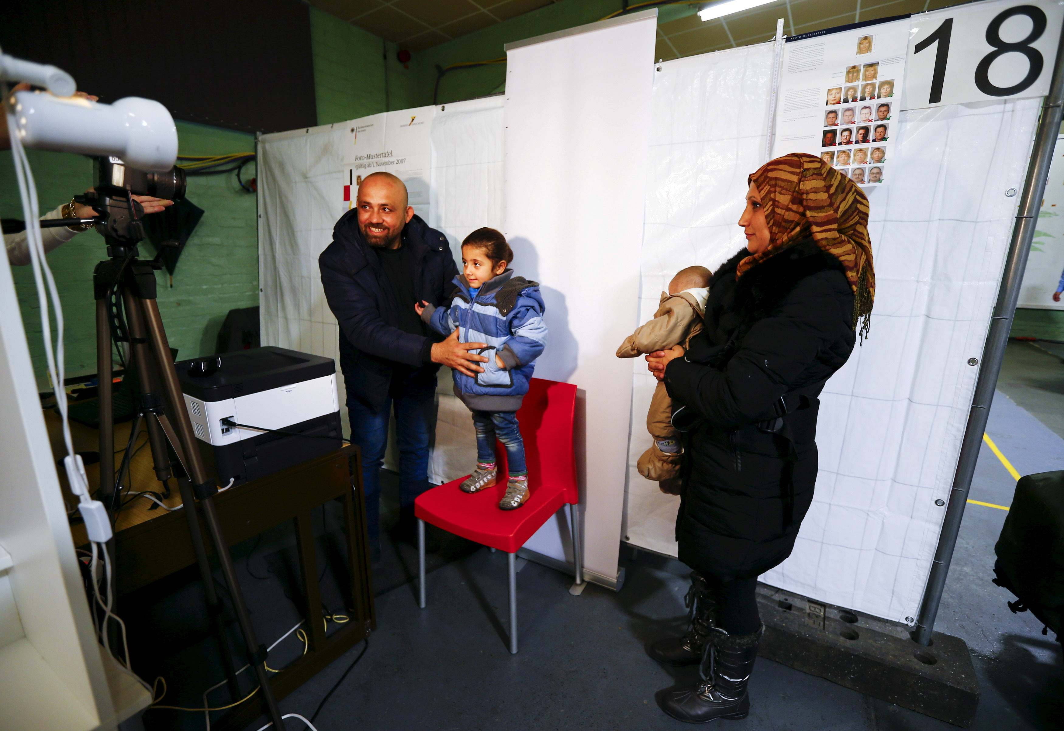 Three year-old Syrian girl Malak stands on a chair for a registration image as her parents Wafy Al-Hamoud Alkhaldy, 36, and his wife Asma Al Saleh, 33, from the eastern Syrian town of Deir ez-Zor are being registered for the so-called
