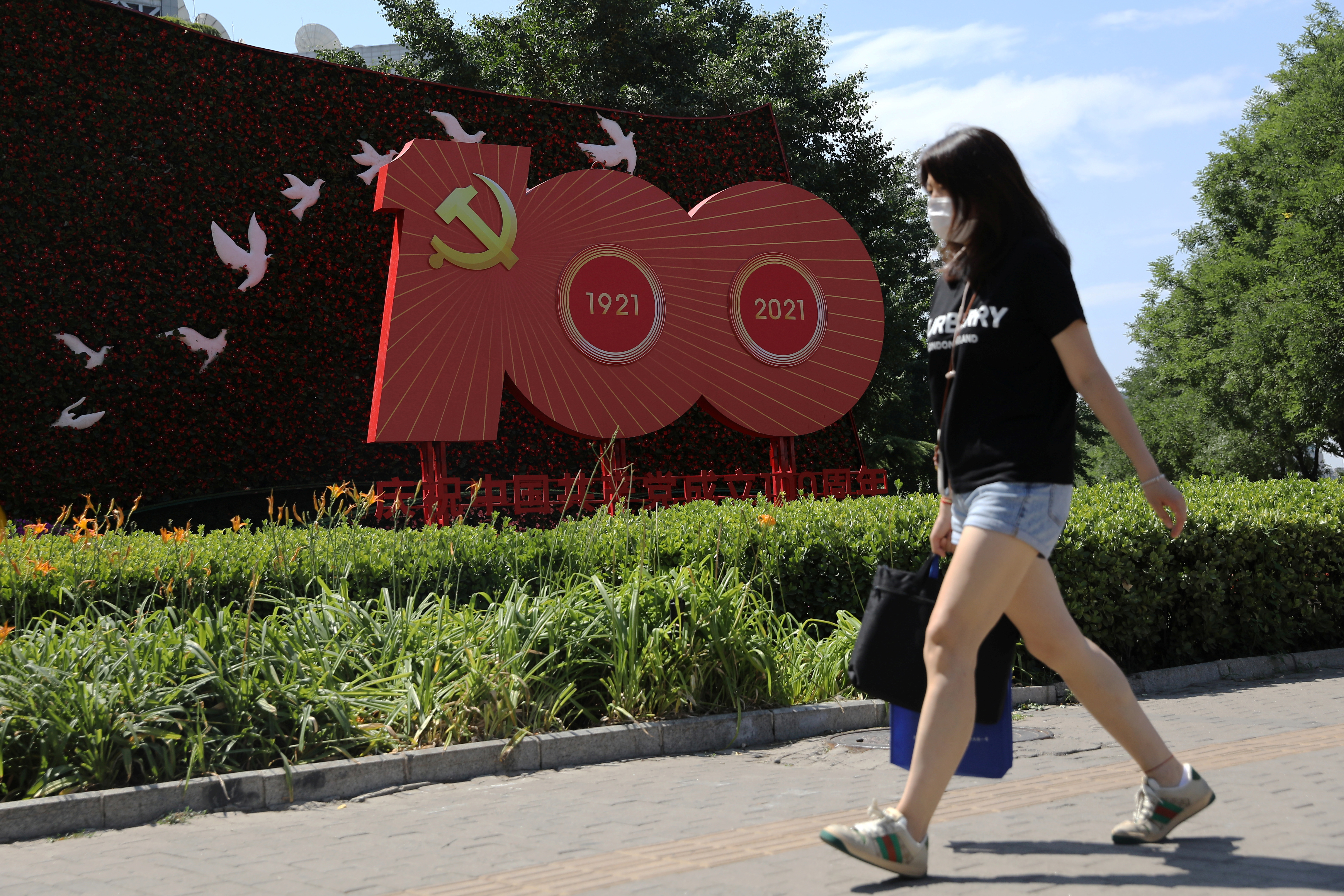 A woman walks past an installation marking the 100th anniversary of the founding of the Chinese Communist Party of China, in Beijing, China June 21, 2021.  REUTERS/Tingshu Wang