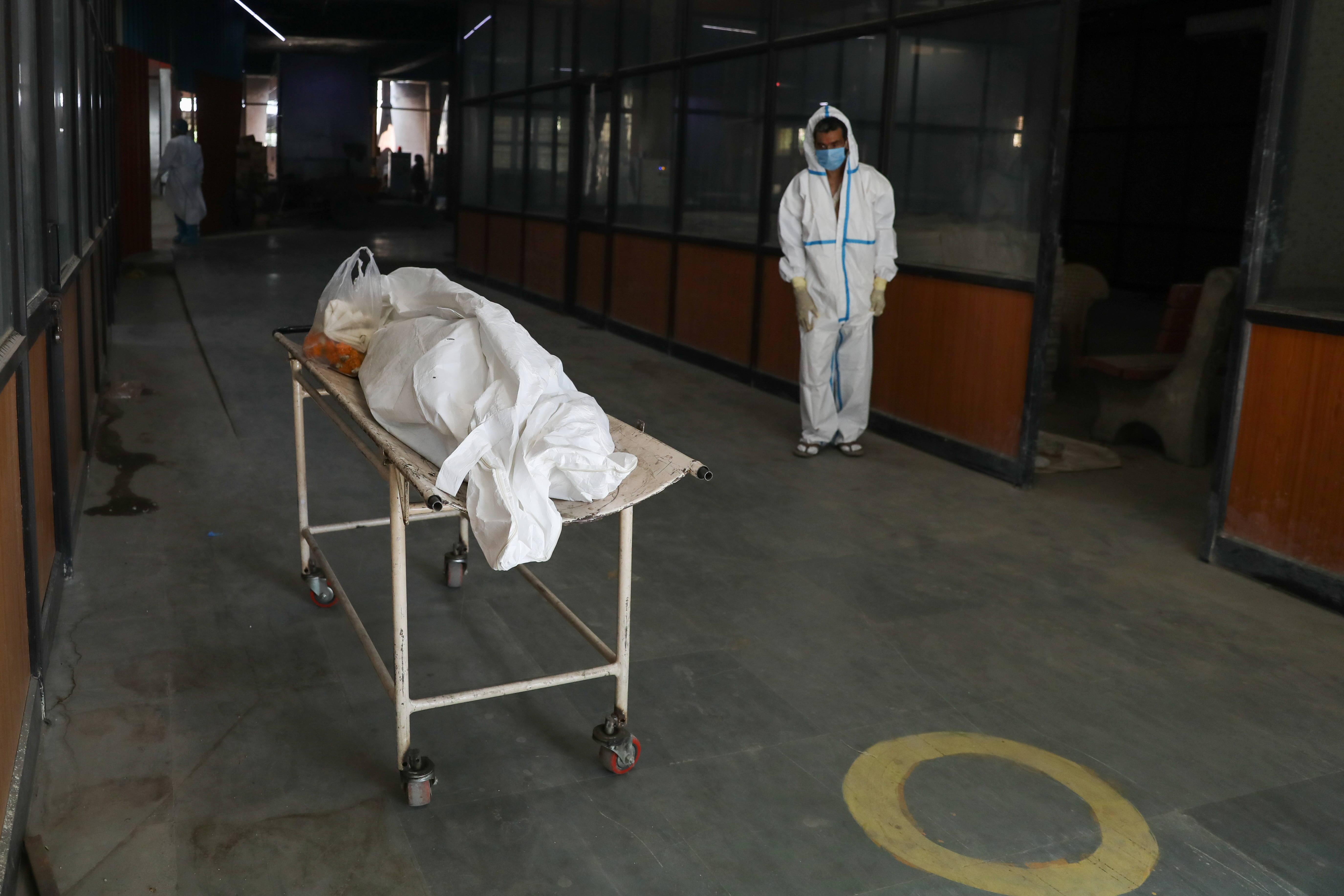 A man wearing personal protection equipment (PPE) waits next to the body of his mother, who died from the coronavirus disease (COVID-19), at a crematorium in New Delhi, India, April 9, 2021. REUTERS/Anushree Fadnavis