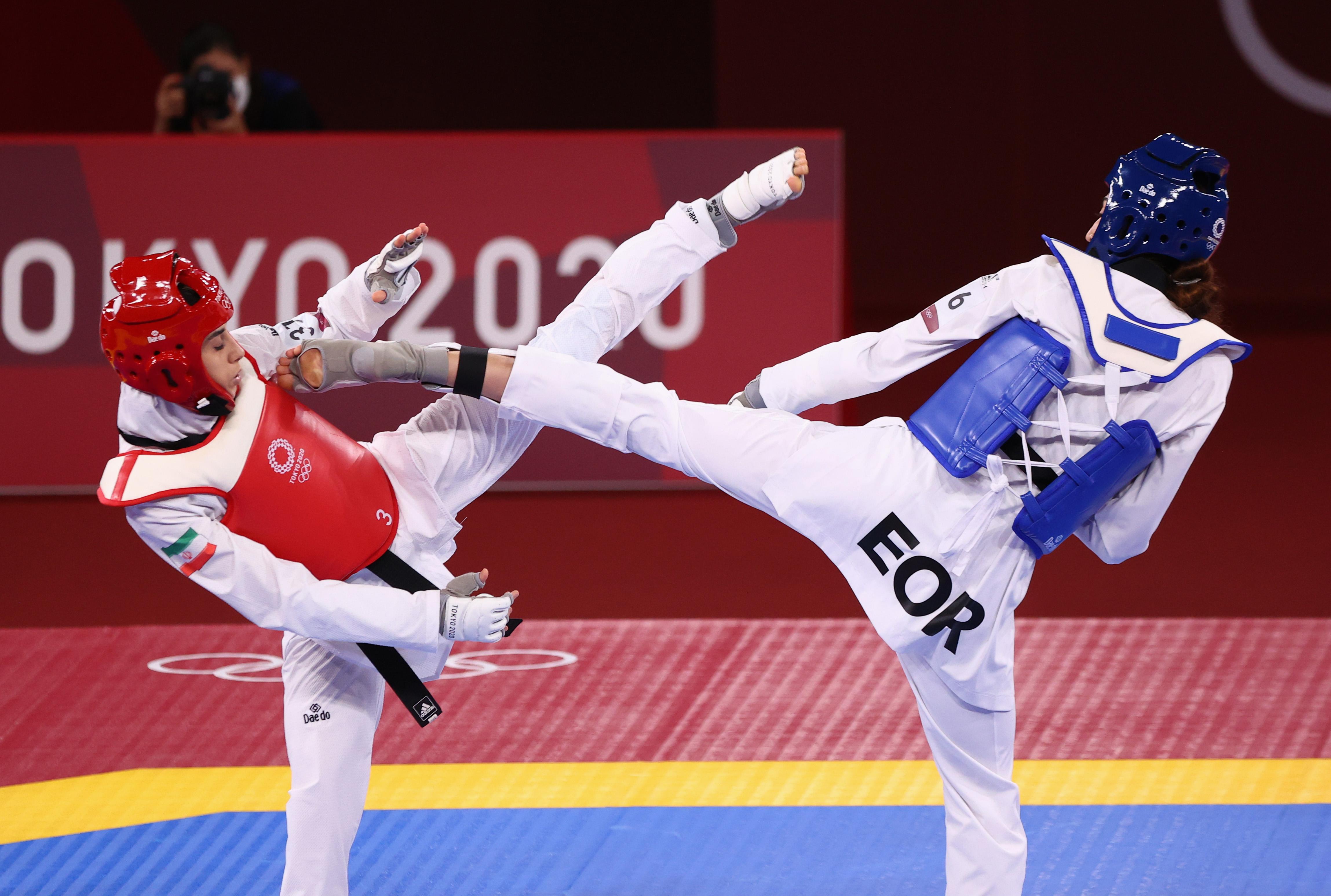 Tokyo 2020 Olympics - Taekwondo - Women's 57kg - Qualification Contest - Makuhari Messe Hall A, Chiba, Japan - July 25, 2021. Kimia Alizadeh of the Refugee Olympic Team in action against Nahid Kiyanichandeh of Iran REUTERS/Murad Sezer