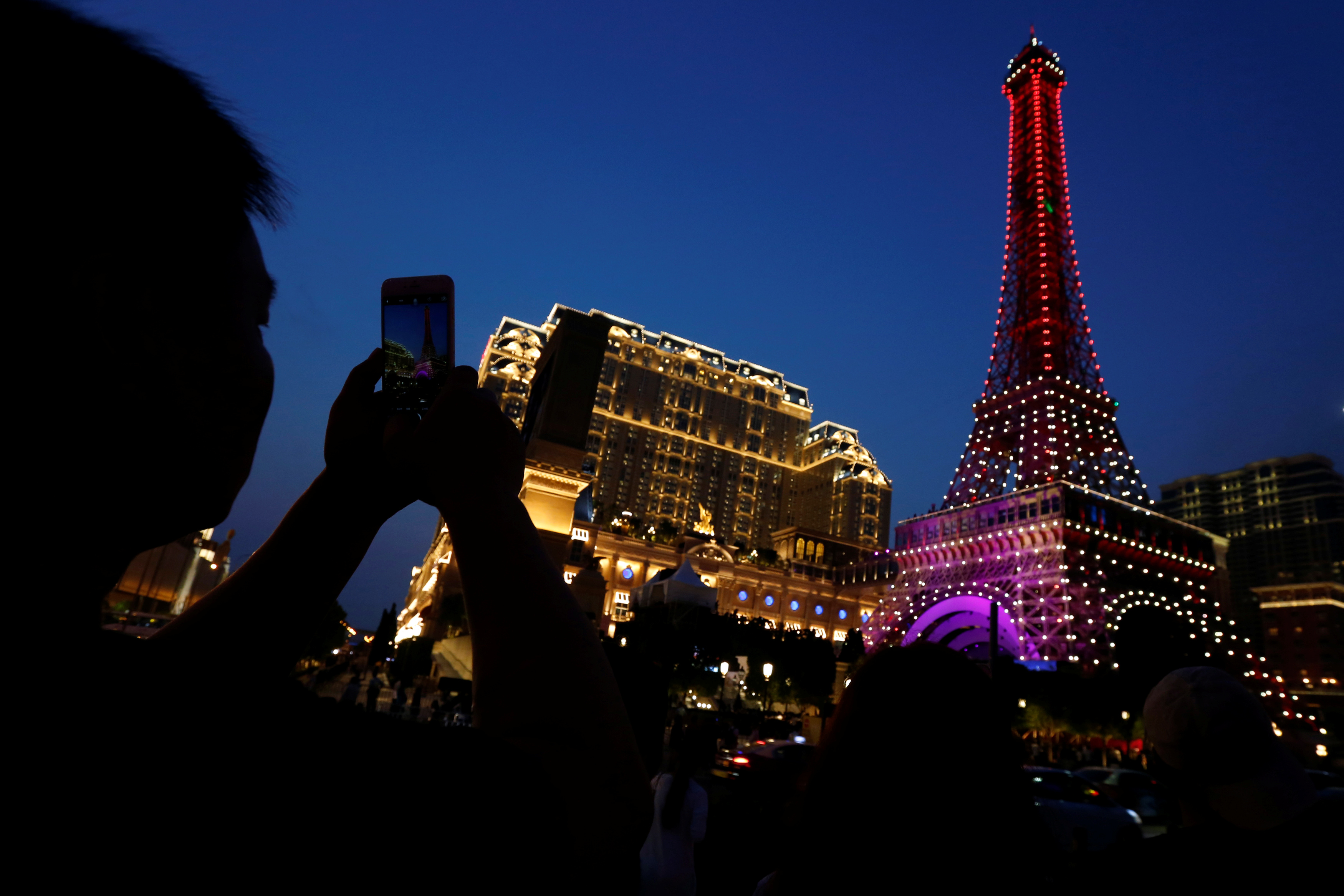 A man takes a photo of a replica of Eiffel Tower outside Parisian Macao as part of the Las Vegas Sands development in Macau, China September 13, 2016.