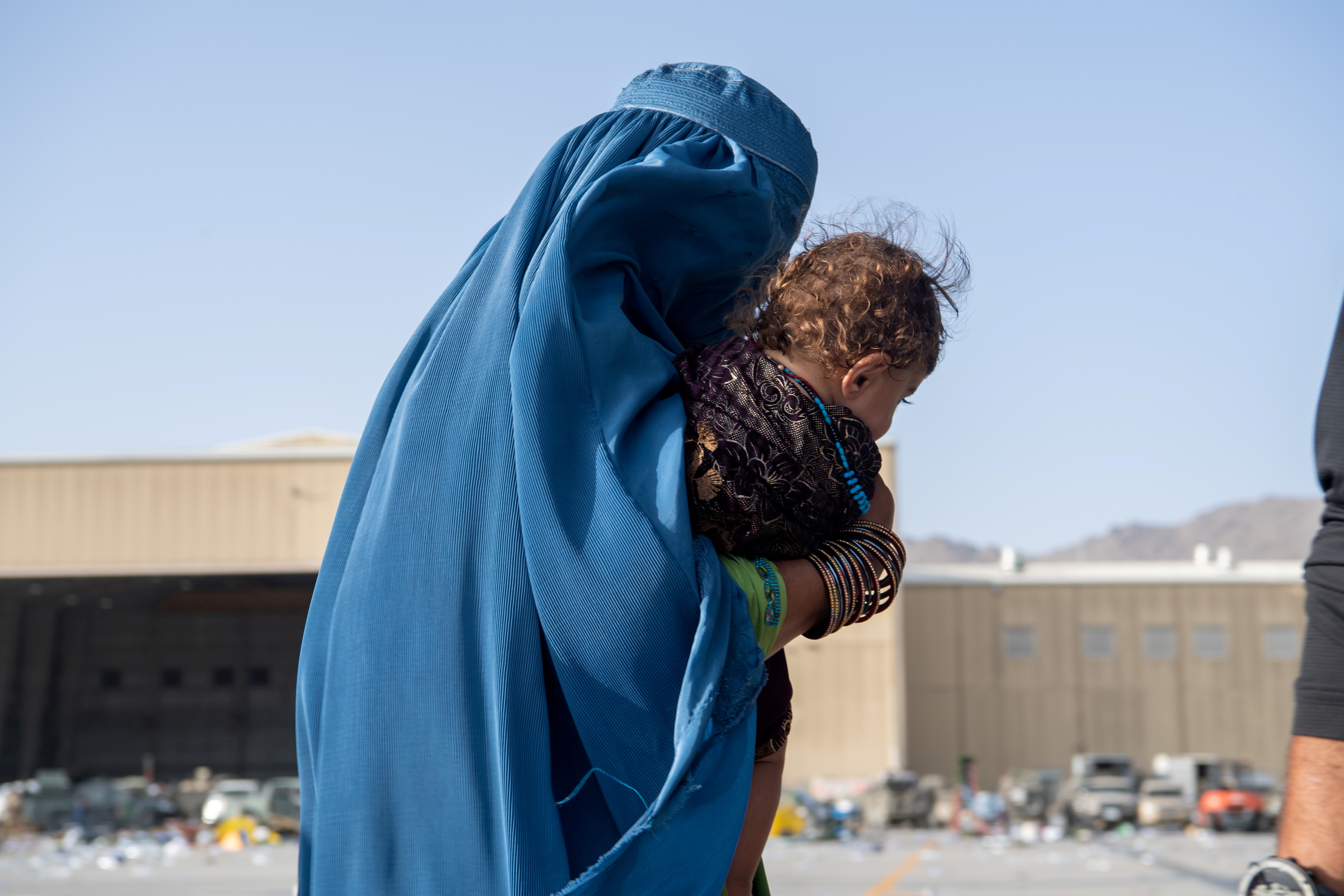 A woman carries a child as passengers board a U.S. Air Force C-17 Globemaster III assigned to the 816th Expeditionary Airlift Squadron in support of the Afghanistan evacuation at Hamid Karzai International Airport in Kabul, Afghanistan, August 24, 2021. Picture taken August 24, 2021. U.S. Air Force/Master Sgt. Donald R. Allen/Handout via REUTERS