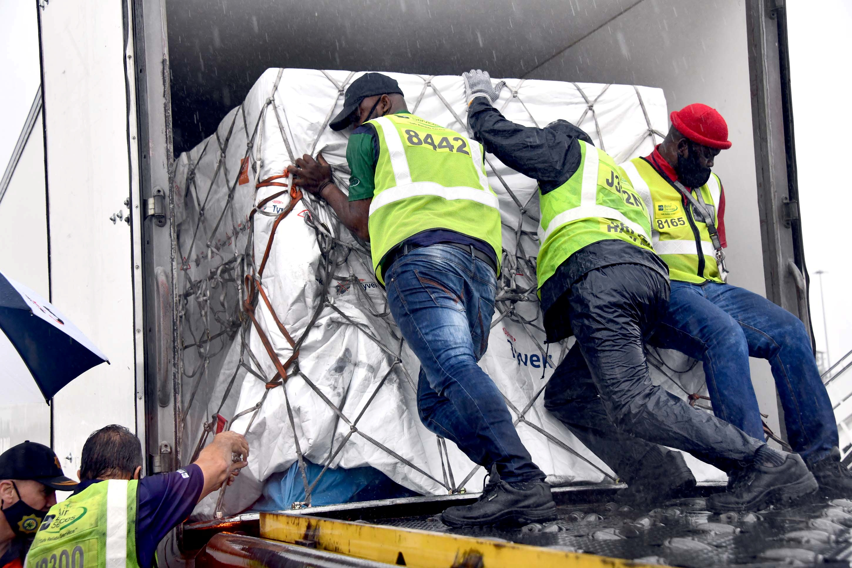 Workers load South Africa's first coronavirus disease (COVID-19) vaccine doses as they arrive at OR Tambo airport in Johannesburg, South Africa, in this handout picture taken February 1, 2021. Elmond Jiyane for GCIS/Handout via REUTERS.