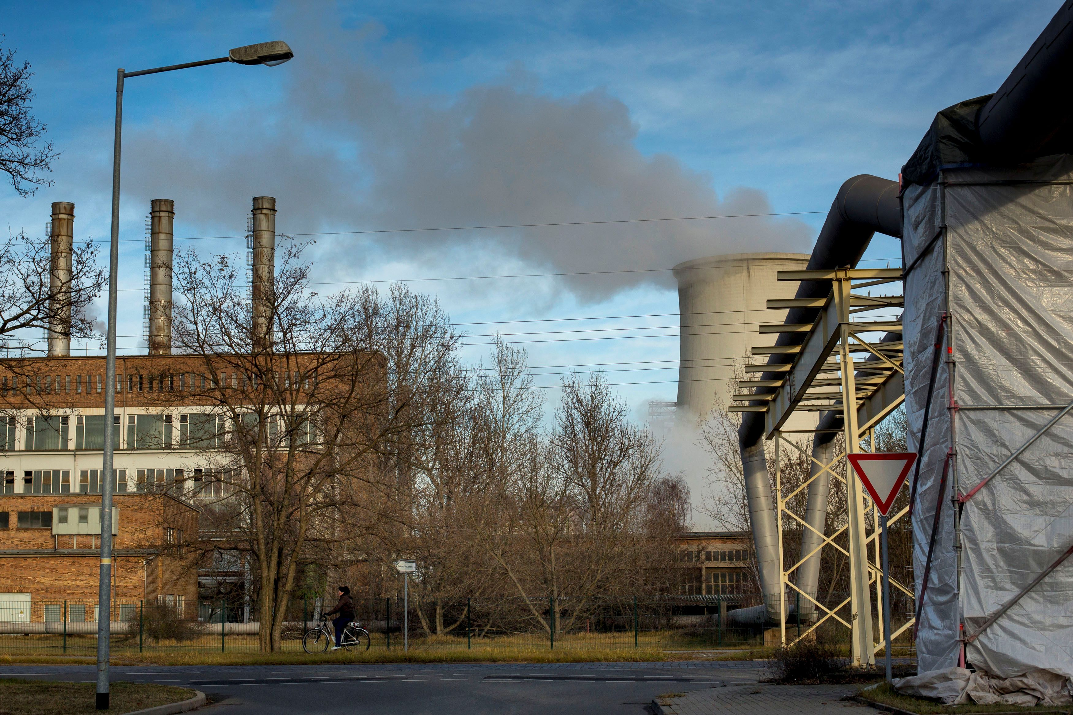 A woman cycles past a power station that is attached to the ArcelorMittal steel factory in Eisenhuettenstadt, 124 km (77 miles) east of Berlin November 26, 2012.REUTERS/Thomas Peter/File Photo