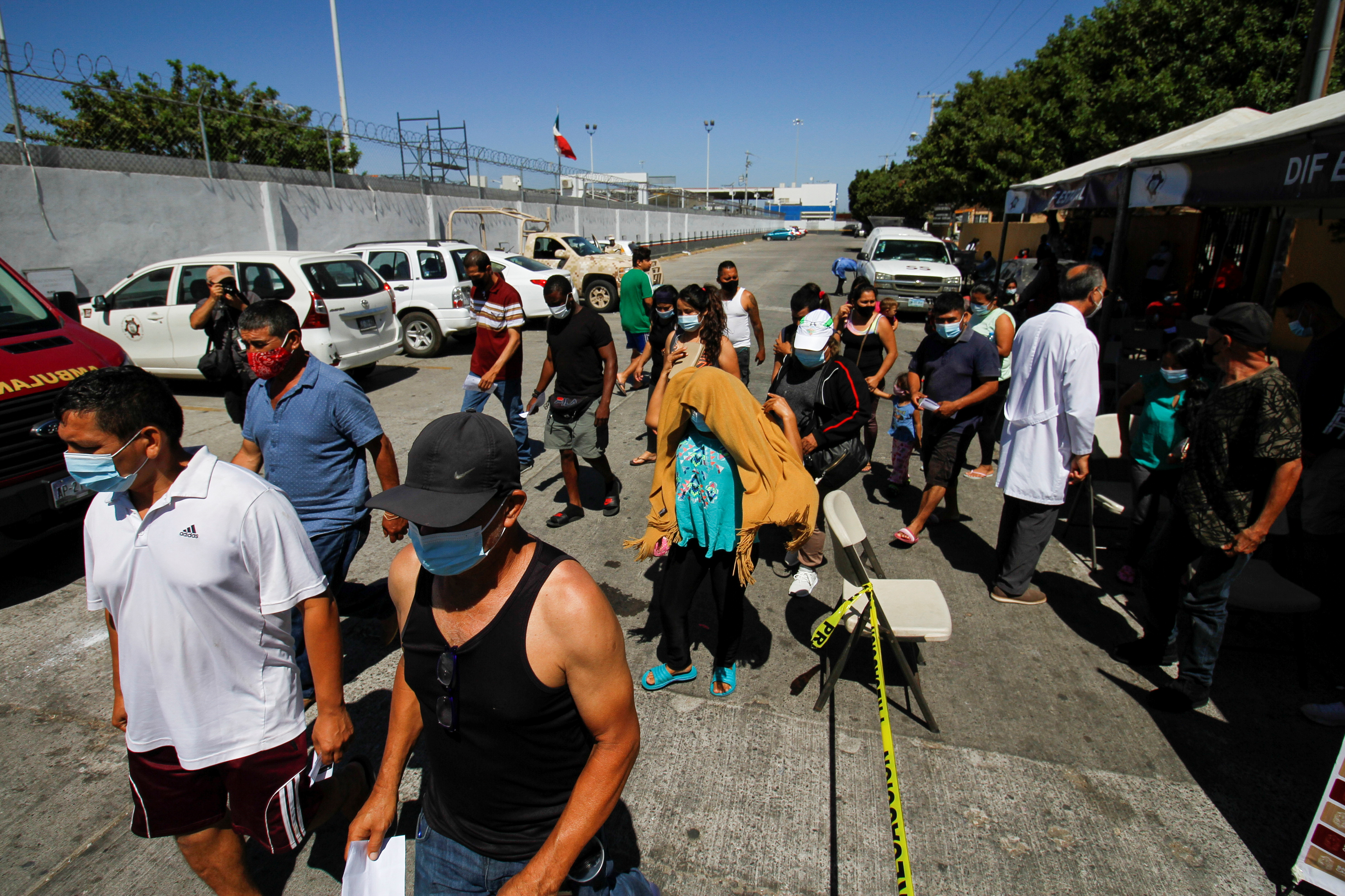 Migrants camping at the El Chaparral border port of entry with the U.S. leave a vaccination point after receiving a dose of the Pfizer BioNTech coronavirus disease (COVID-19) vaccine, amid Republican criticism that the Delta variant is spreading in southern U.S. states because of increased border crossings, in Tijuana, Mexico August 3, 2021. REUTERS/Jorge Duenes