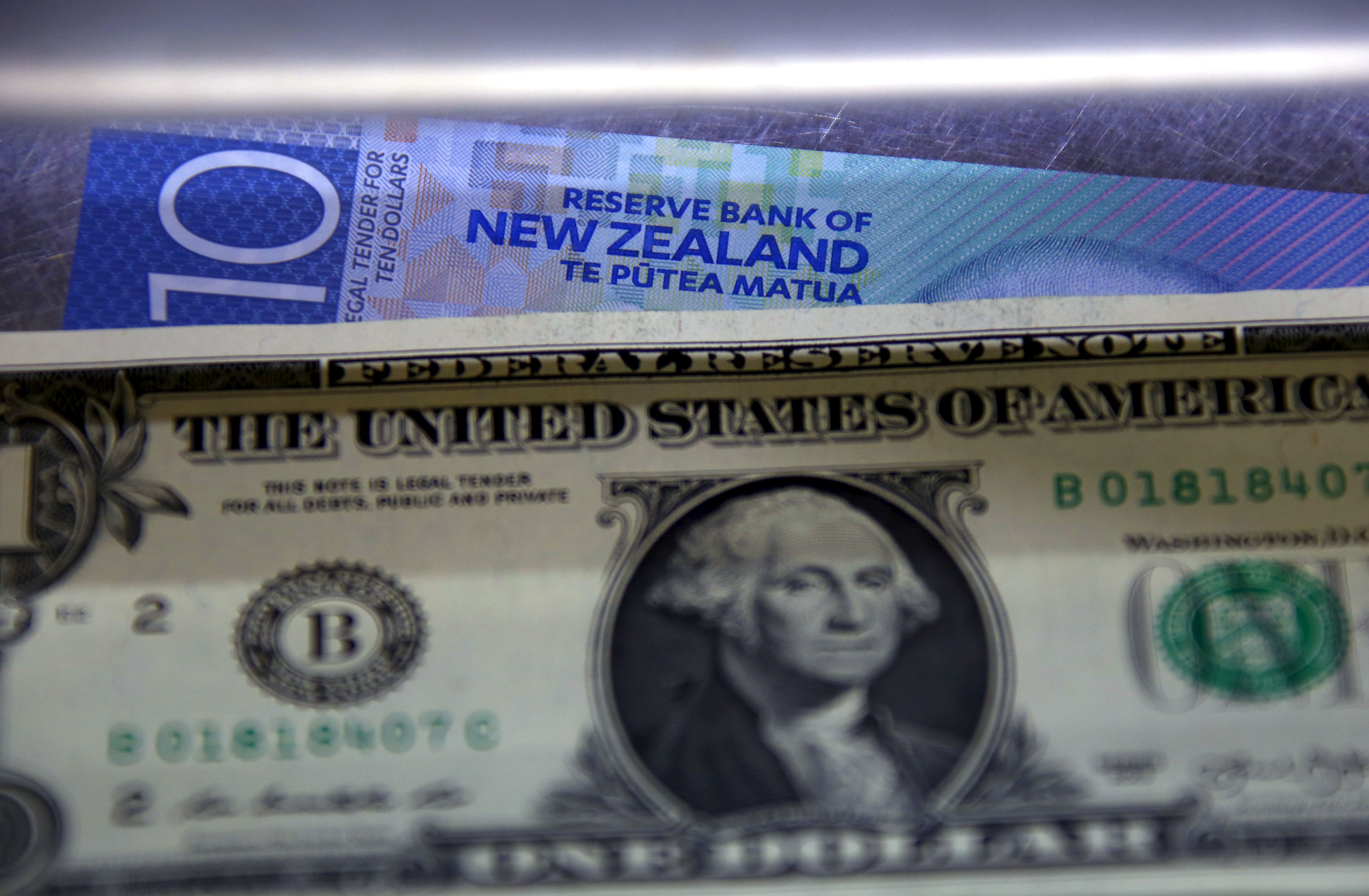 A New Zealand ten dollar note sits underneath a United States one dollar bill in the window of a currency exchange teller in Sydney, Australia, March 10, 2016. REUTERS/David Gray