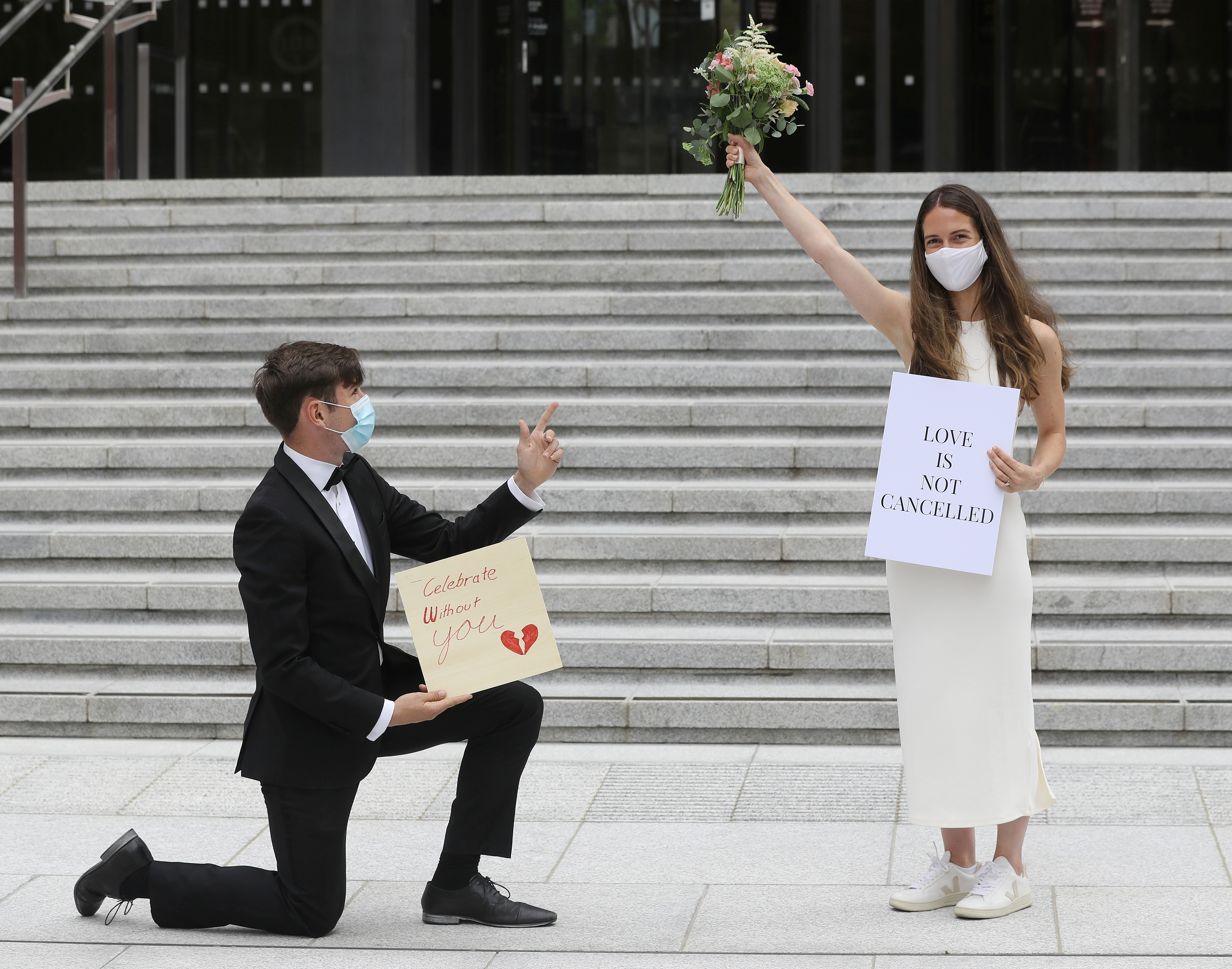 Tony Barry and Anna Killeen hold up signs at a protest march to Government Buildings in a bid to allow up to 100 guests to attend weddings this year in Dublin, Ireland, July 27, 2021. REUTERS/Lorraine O'Sullivan