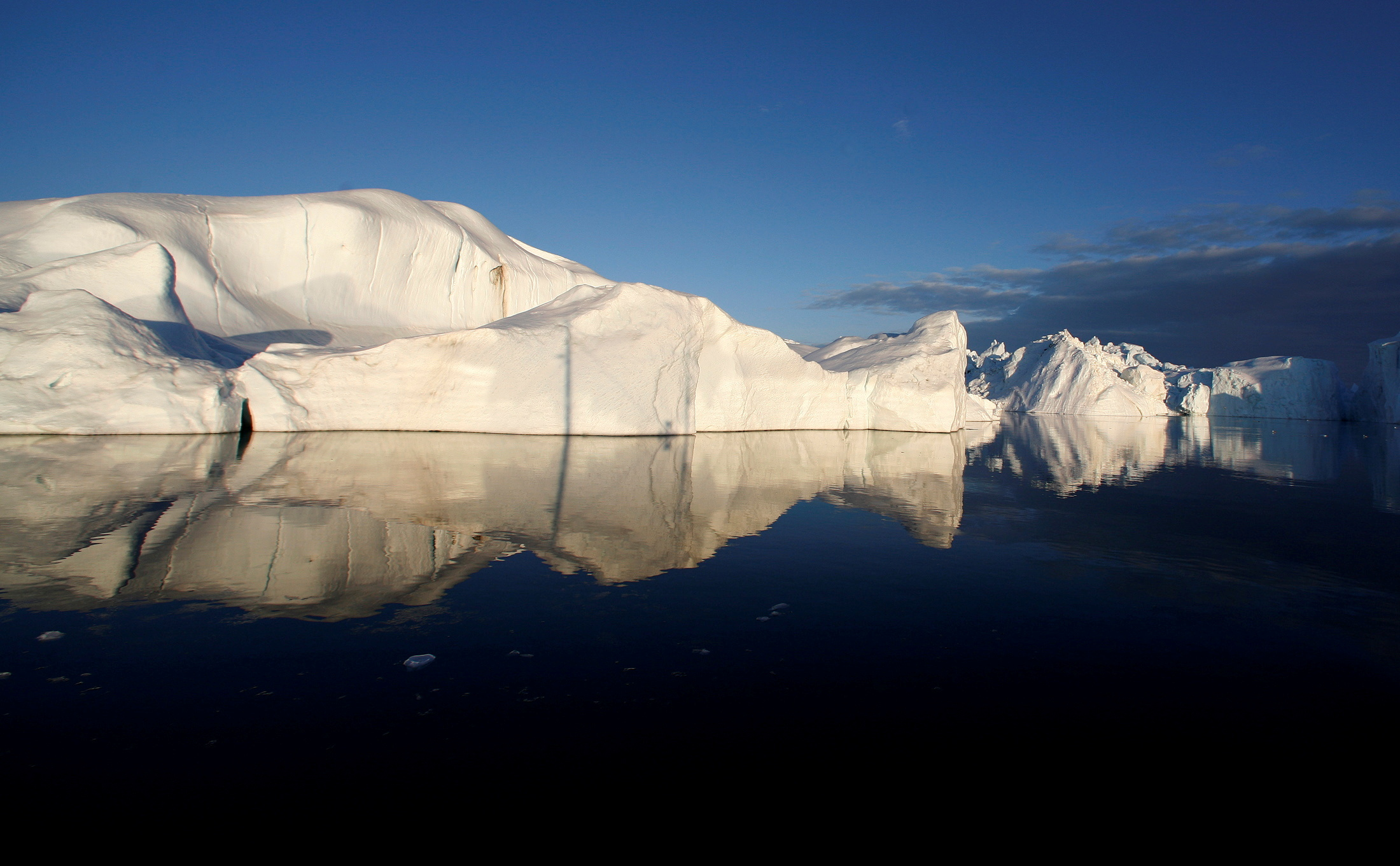 Icebergs are reflected in the calm waters at the mouth of the Jakobshavn ice fjord near Ilulissat, Greenland, May 15, 2007.  REUTERS/Bob Strong