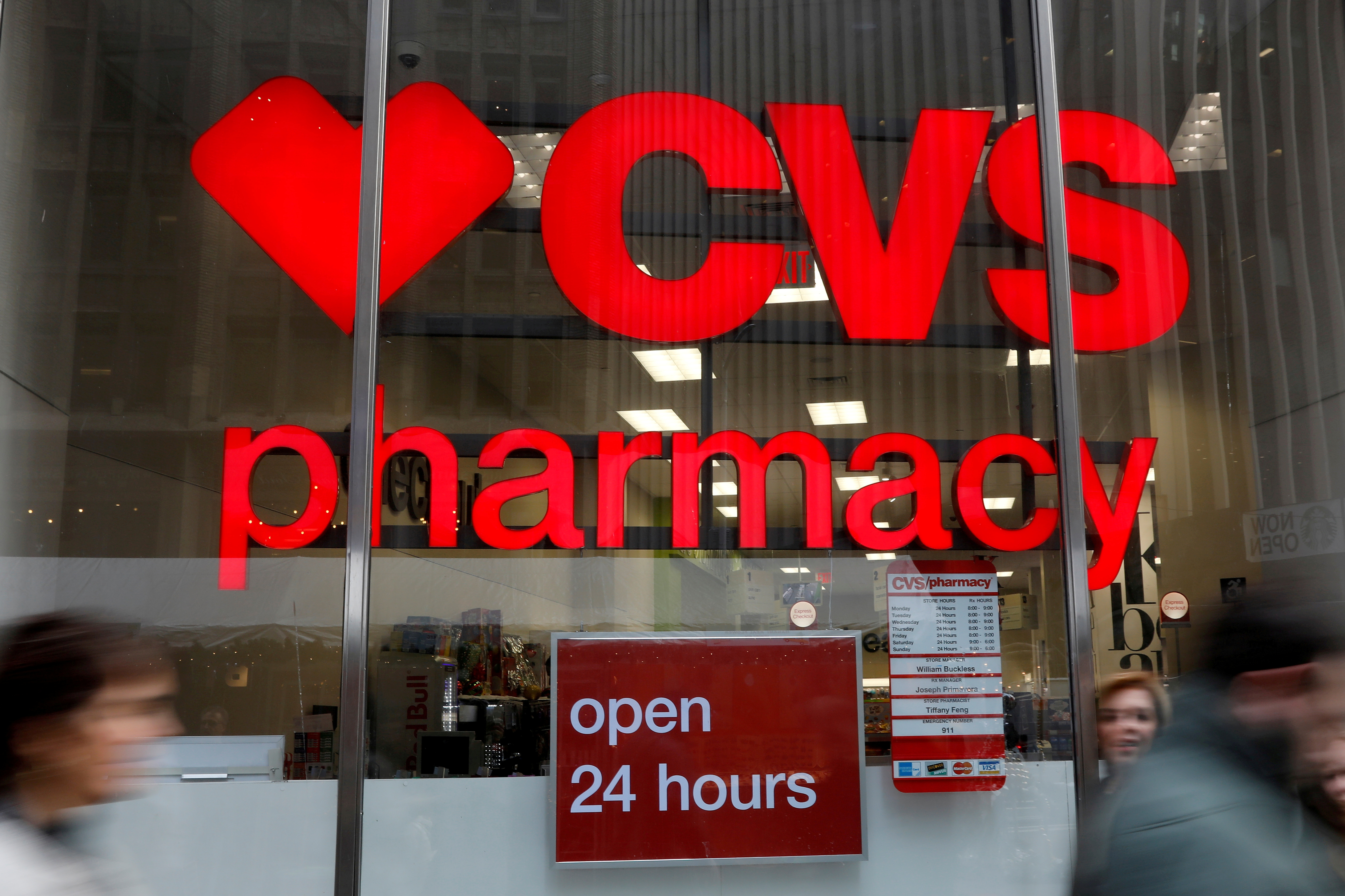 People walk by a CVS Pharmacy store in the Manhattan borough of New York City, New York, U.S., November 30, 2017. REUTERS/Shannon Stapleton