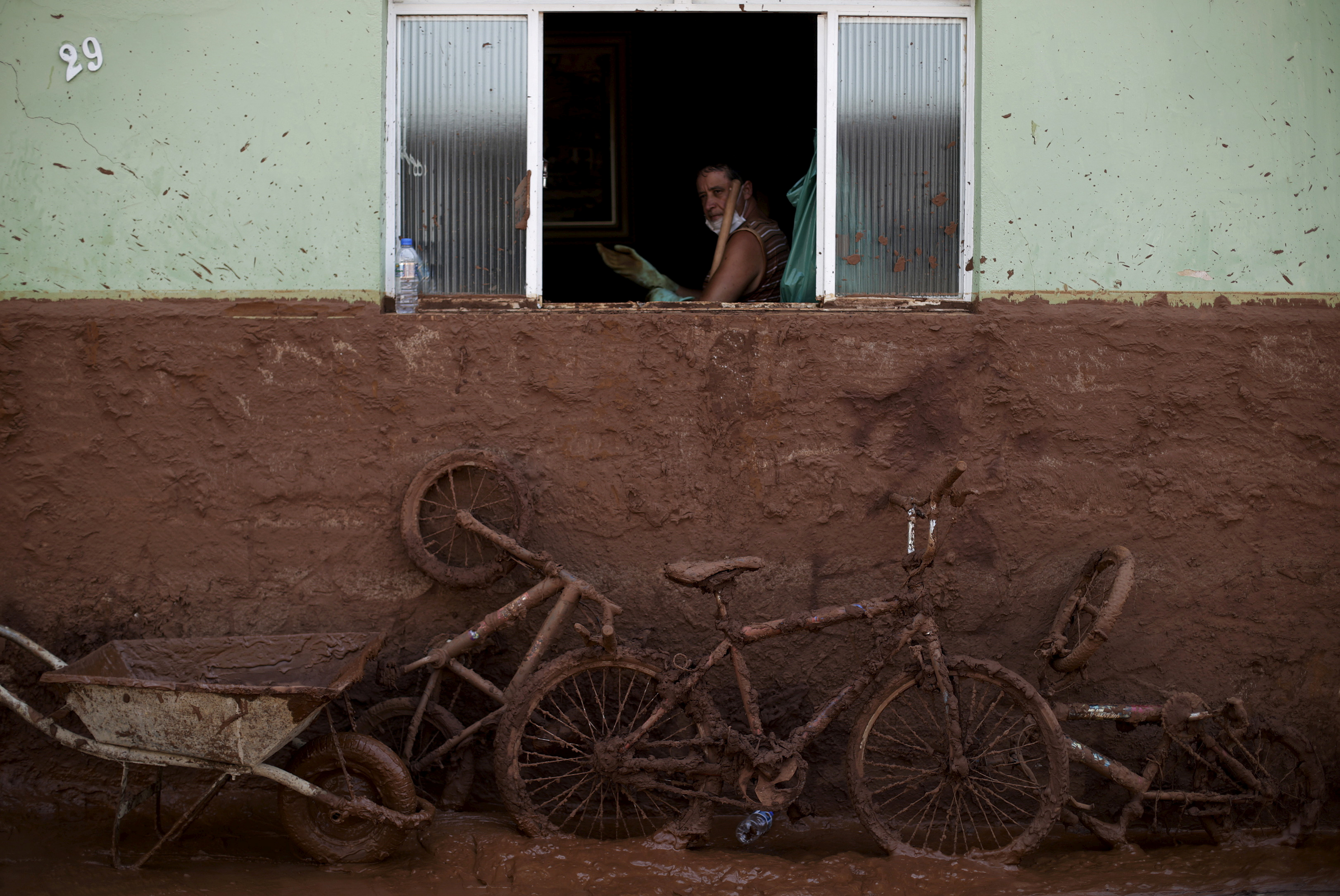 A man works on the cleaning of a house flooded with mud after a dam, owned by Vale SA and BHP Billiton Ltd burst, in Barra Longa, Brazil, November 7, 2015. REUTERS/Ricardo Moraes/File Photo