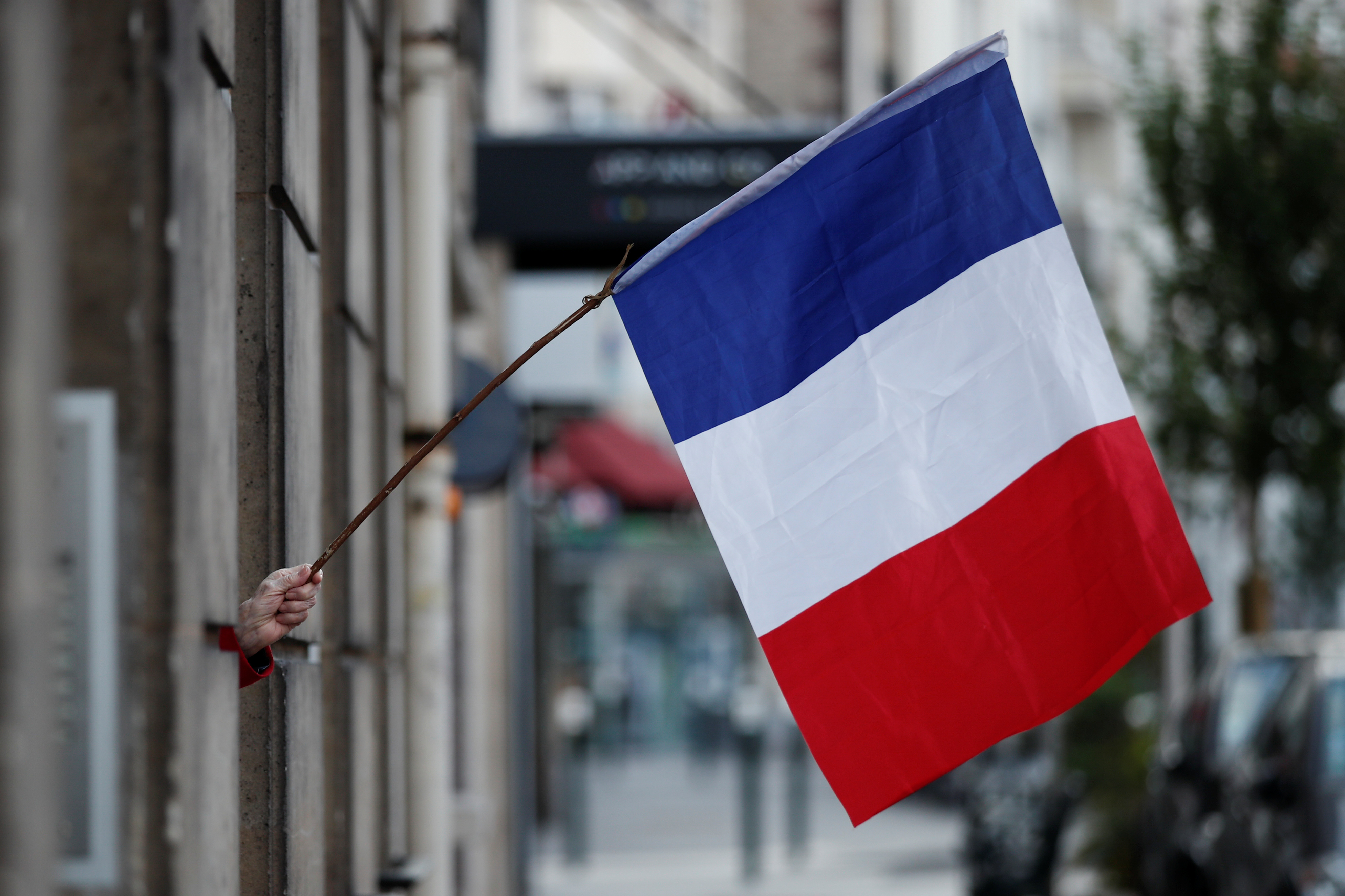A woman waves a French flag from a window to support healthcare workers amid the coronavirus disease (COVID-19) outbreak in Saint-Mande, near Paris, France May 5 2020.
