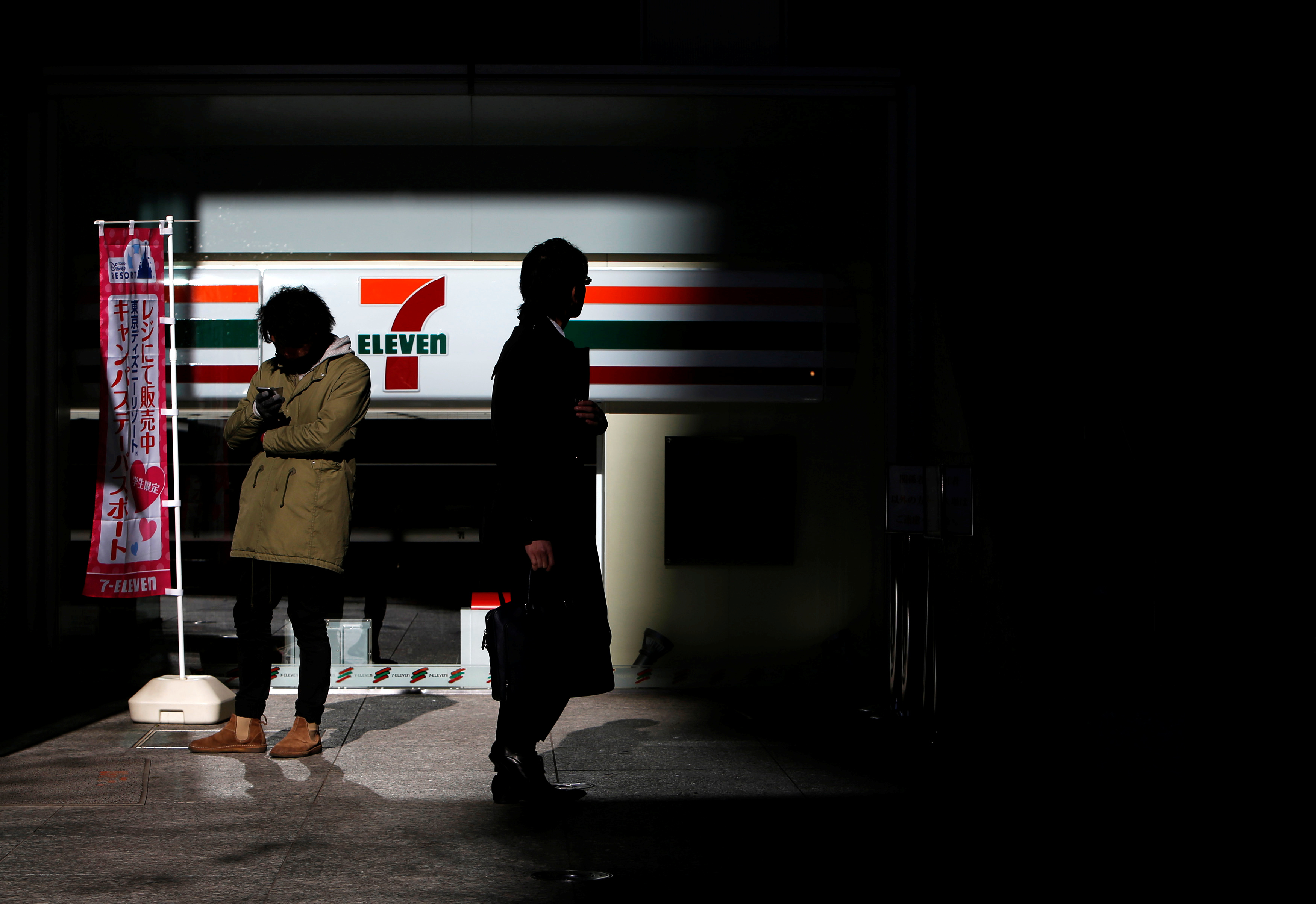 People stand outside a 7-Eleven convenience store outside the headquarters of Seven & I Holdings in Tokyo January 9, 2015. REUTERS/Yuya Shino/File Photo - S1BETFUGTKAB
