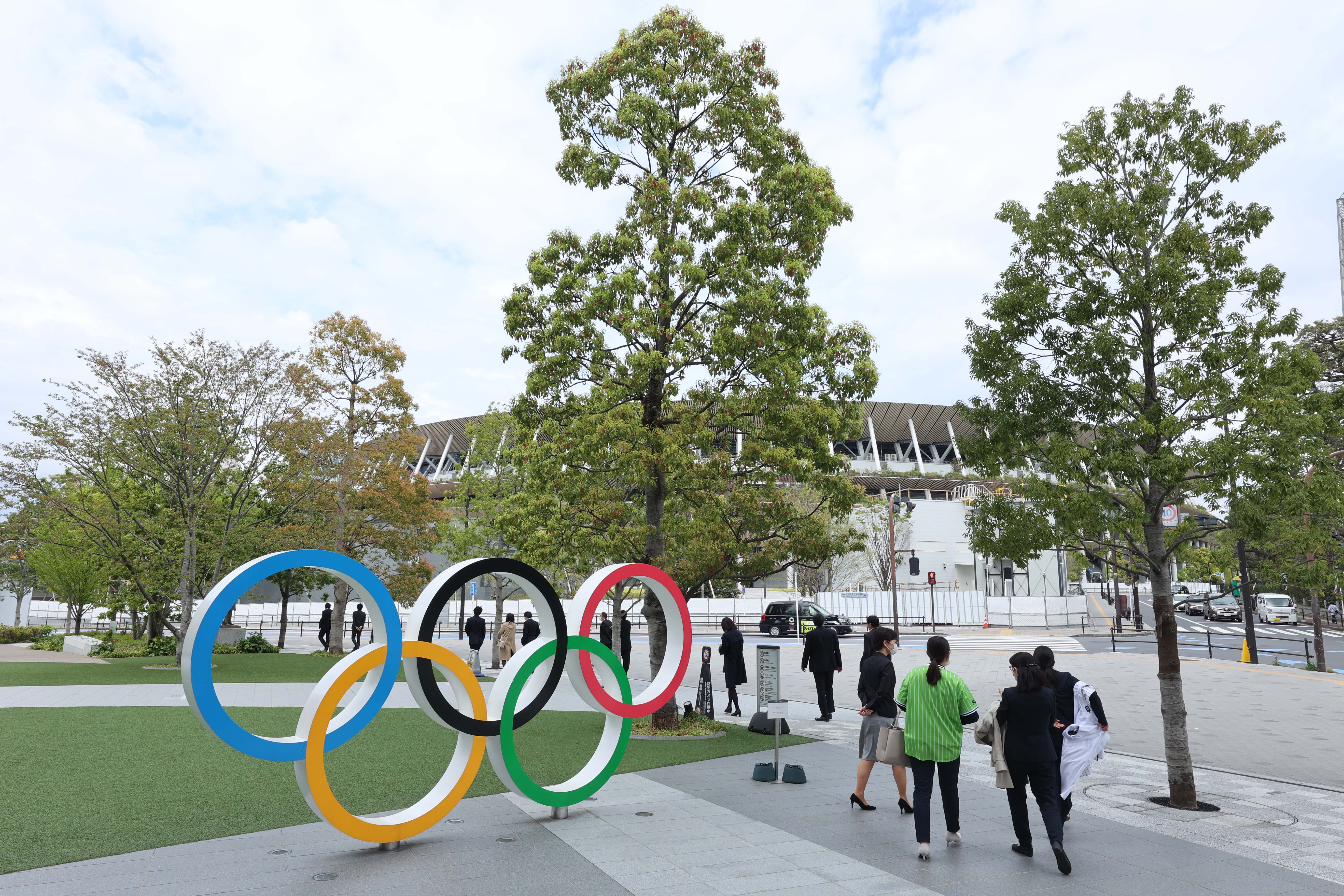 Apr 6, 2021; Tokyo, JAPAN; People walk past the Olympic rings sculpture near the Japan National Stadium in preparation for the Tokyo 2020 Olympic Summer Games set to begin in July 2021. Mandatory Credit: Yukihito Taguchi-USA TODAY Sports
