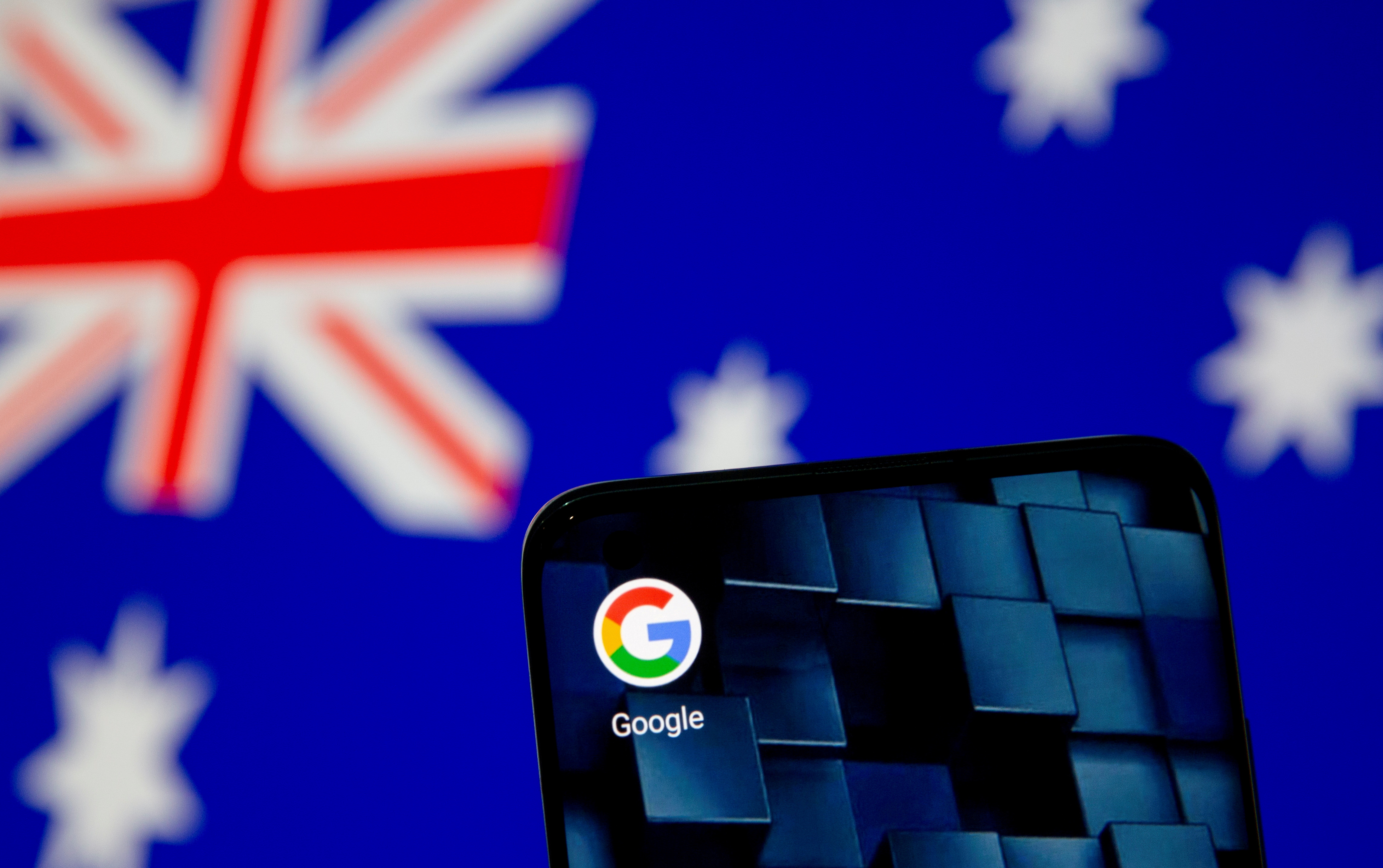 A smartphone with a Google app icon is seen in front of a displayed Australian flag in this illustration, Jan. 22, 2021. REUTERS/Dado Ruvic/Illustration/File Photo/File Photo