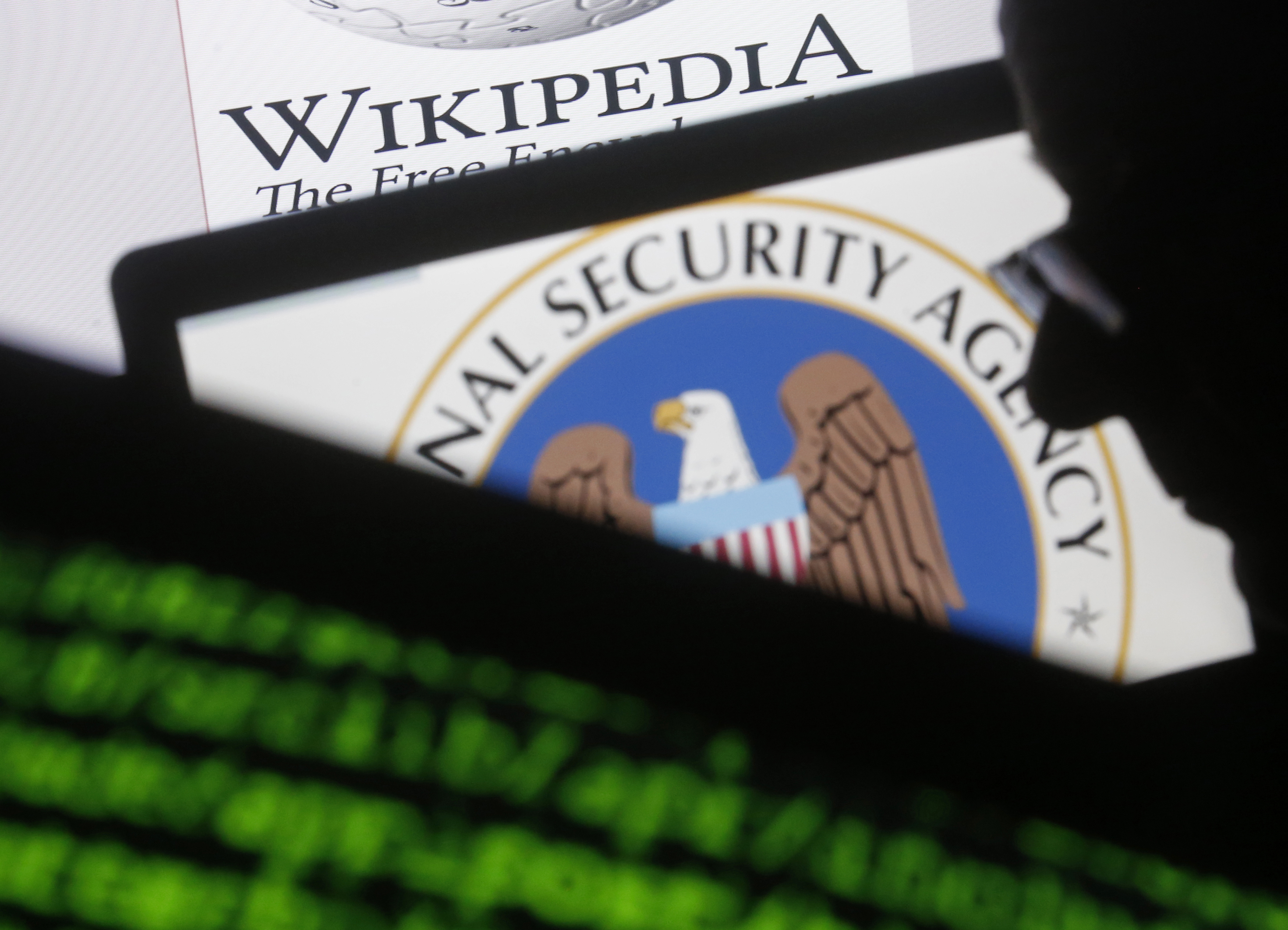 A man is seen near cyber code and the U.S. National Security Agency logo in this photo illustration taken in Sarajevo March 11, 2015. REUTERS/Dado Ruvic/Files
