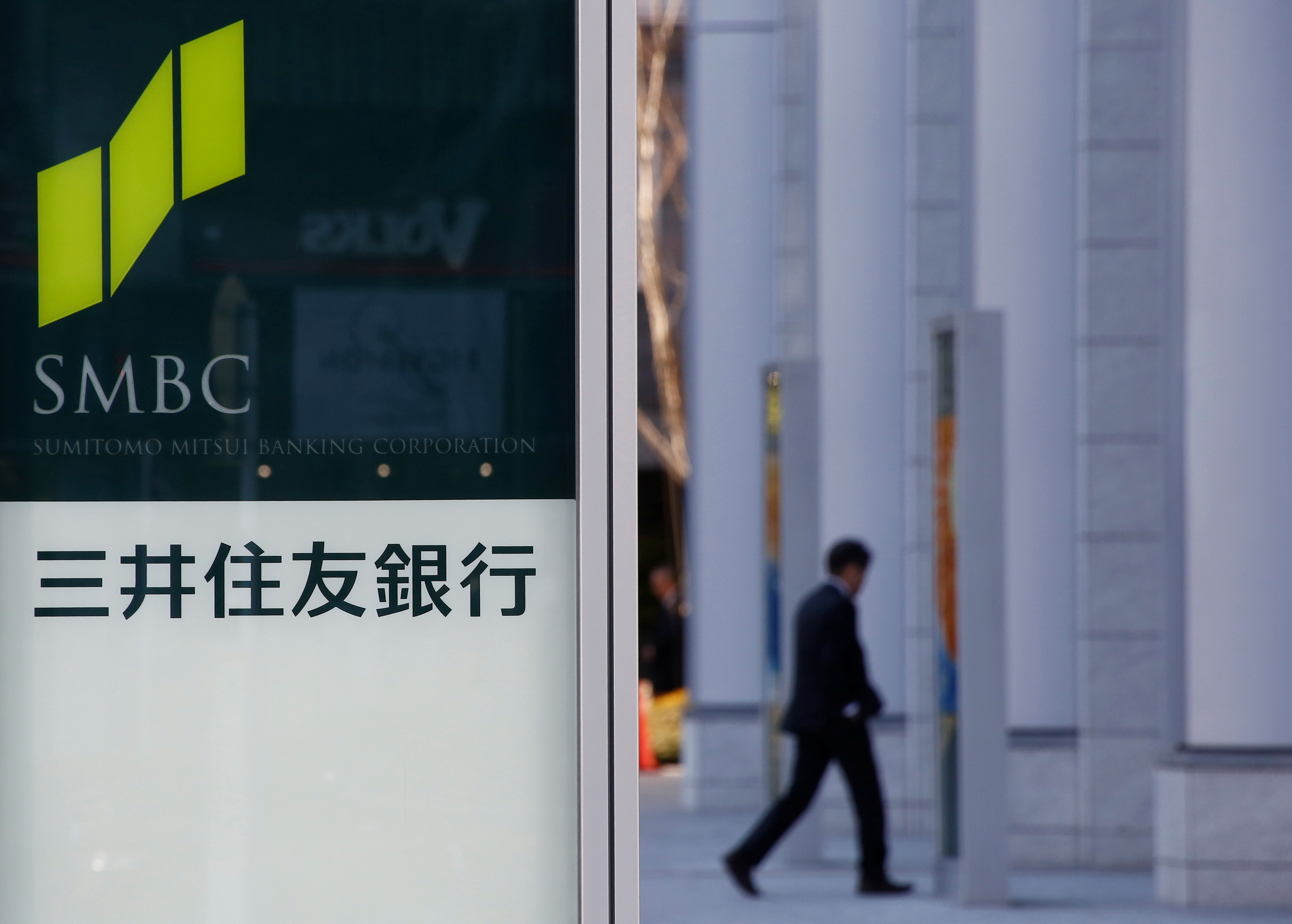 A man walk past a signboard of Sumitomo Mitsui Banking Corporation's signboard at its branch in Tokyo, Japan, January 25, 2017. Picture taken on January 25, 2017.REUTERS/Kim Kyung-Hoon