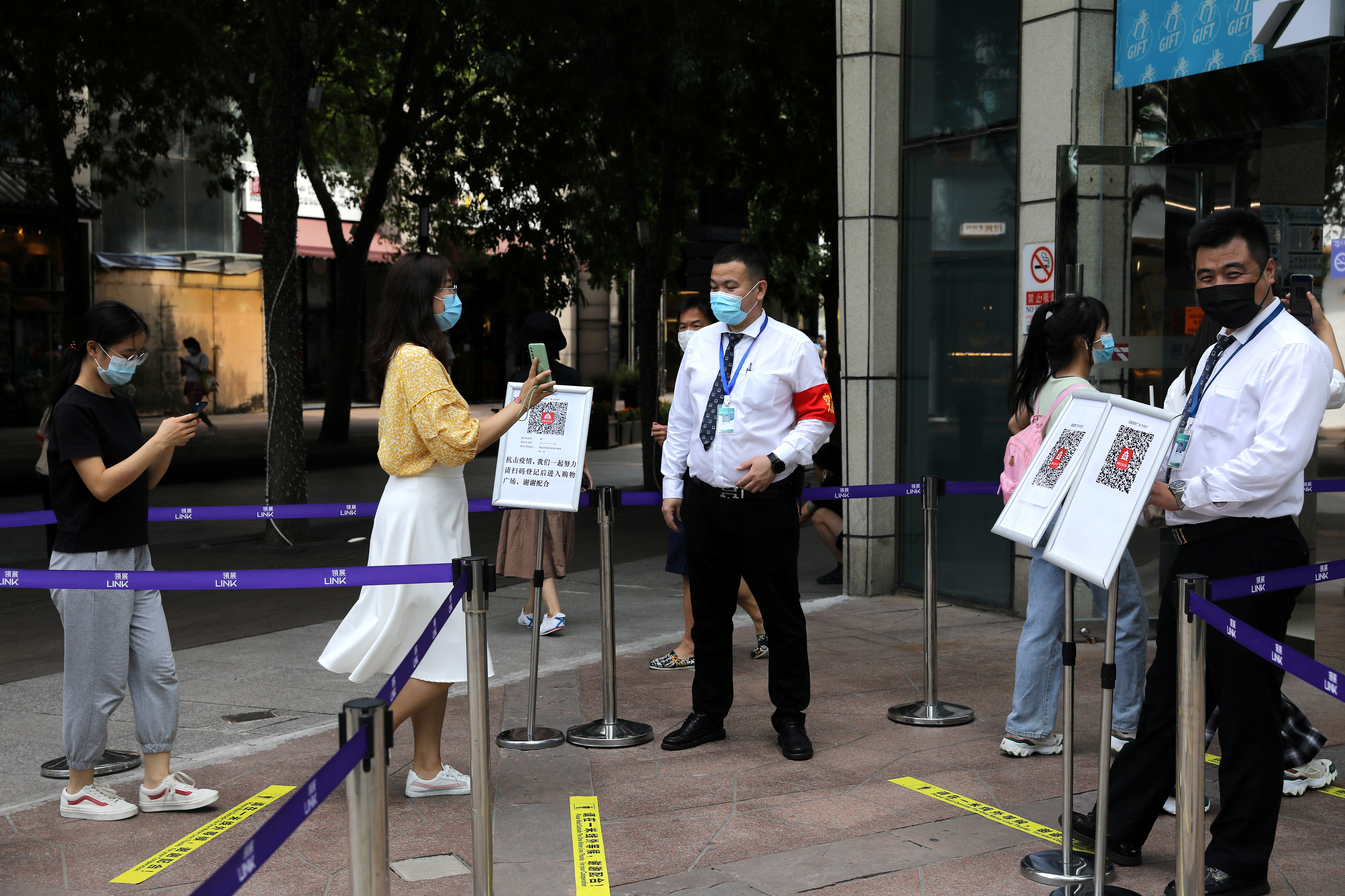 A woman shows her health status on a phone to a security guard, at an entrance of a shopping mall in Beijing, China August 23, 2021. REUTERS/Tingshu Wang/File Photo