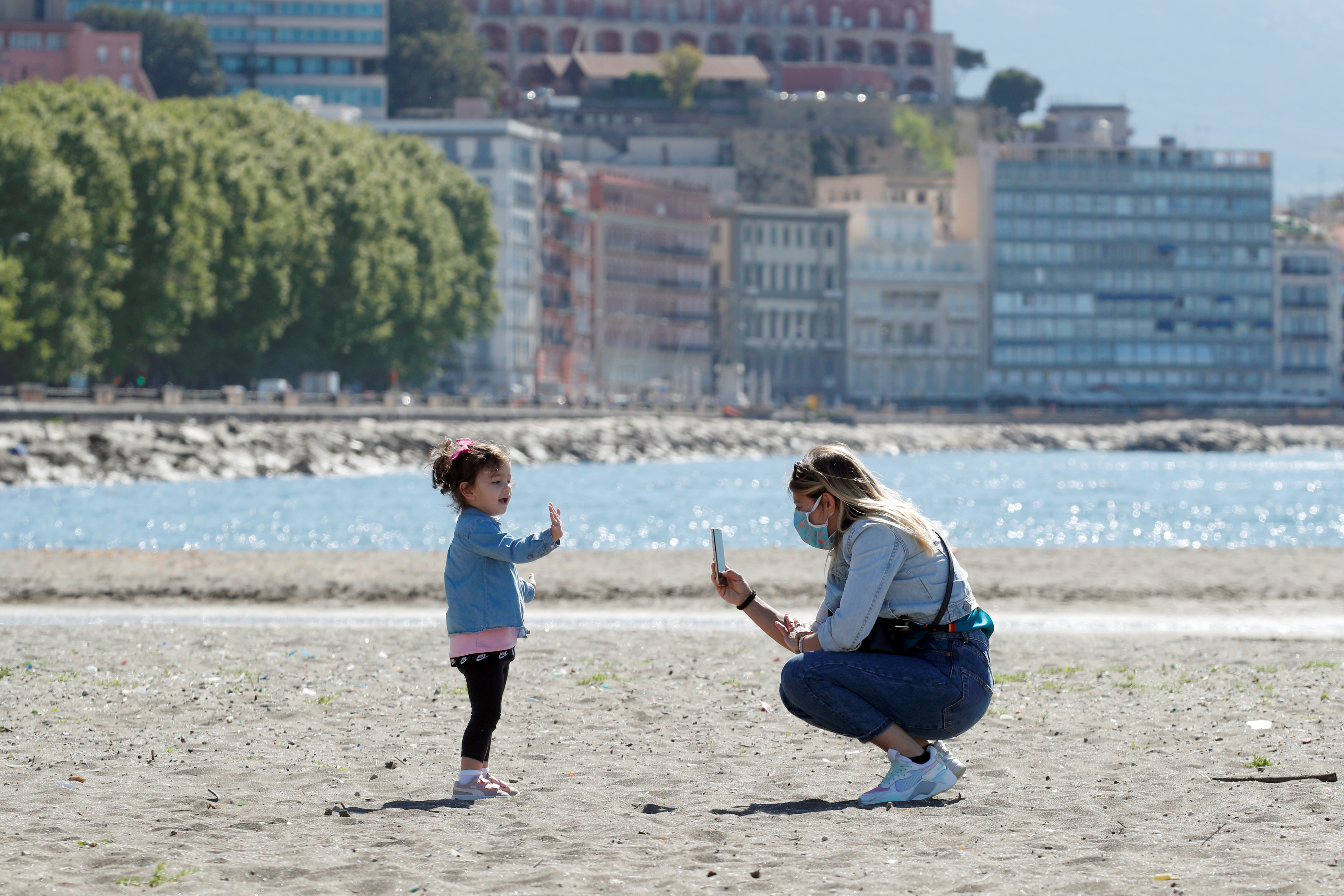 A woman and a child are seen at the beach, as Italy begins a staged end to a nationwide lockdown due to the spread of the coronavirus disease (COVID-19), in Naples, Italy May 4, 2020. REUTERS/Ciro De Luca