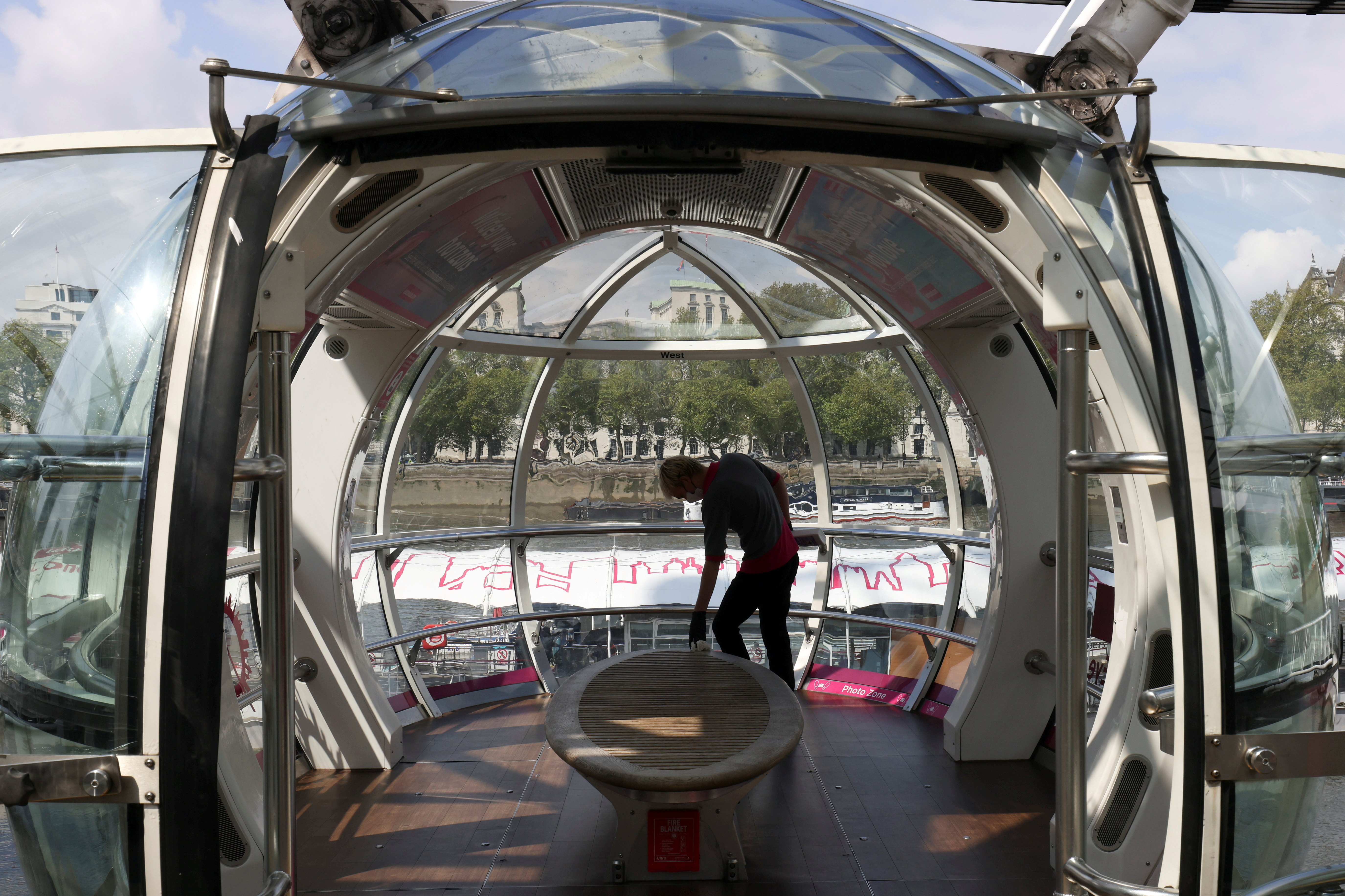 A worker cleans the interior of the London Eye' capsule as the attraction reopens while coronavirus disease (COVID-19) restrictions continue to ease in London, Britain, May 17, 2021. REUTERS/Tom Nicholson