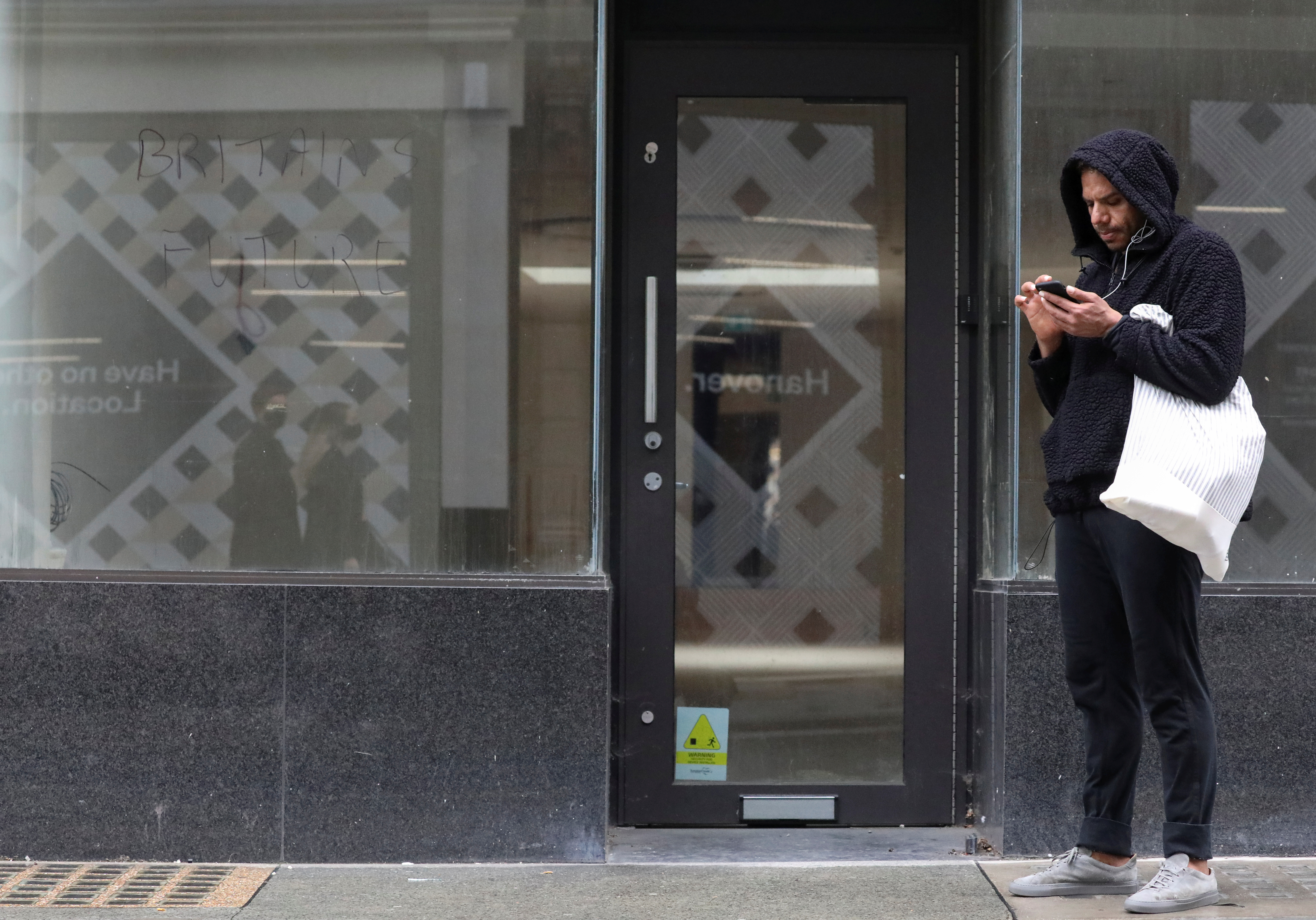 A man looks at his phone next to a shut down store, amid the outbreak of the coronavirus disease (COVID-19), in London, Britain October 13, 2020. REUTERS/Simon Dawson