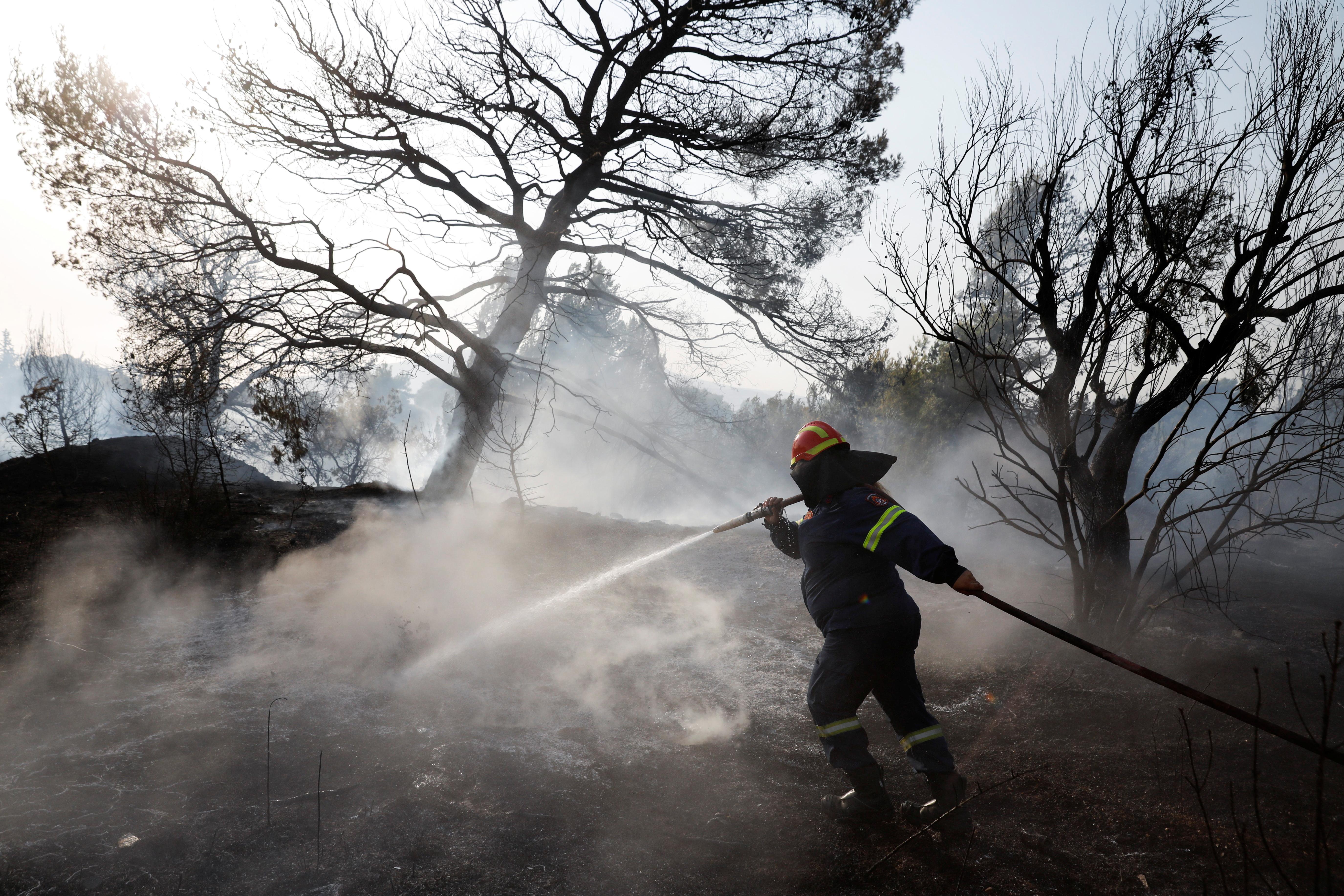 Vatrogasac prska vodu u pokušaju da pomogne u suzbijanju požara u predgrađu Varympompi sjeverno od Atene, Grčka, 4. kolovoza 2021. REUTERS/Costas Baltas