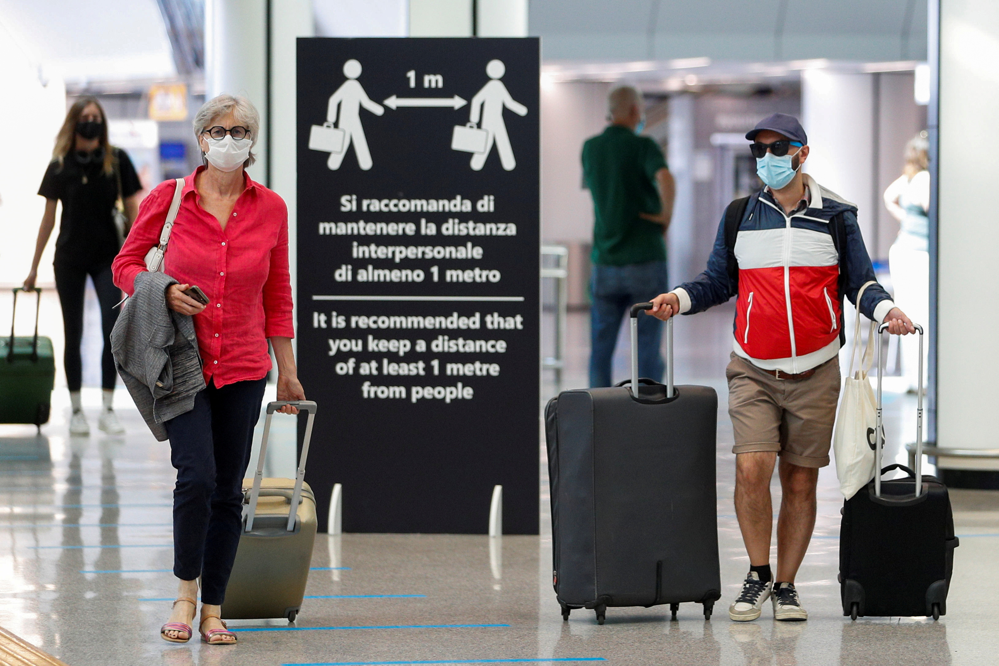 Passengers wearing protective face masks walk at Fiumicino Airport on the day EU governments agreed a