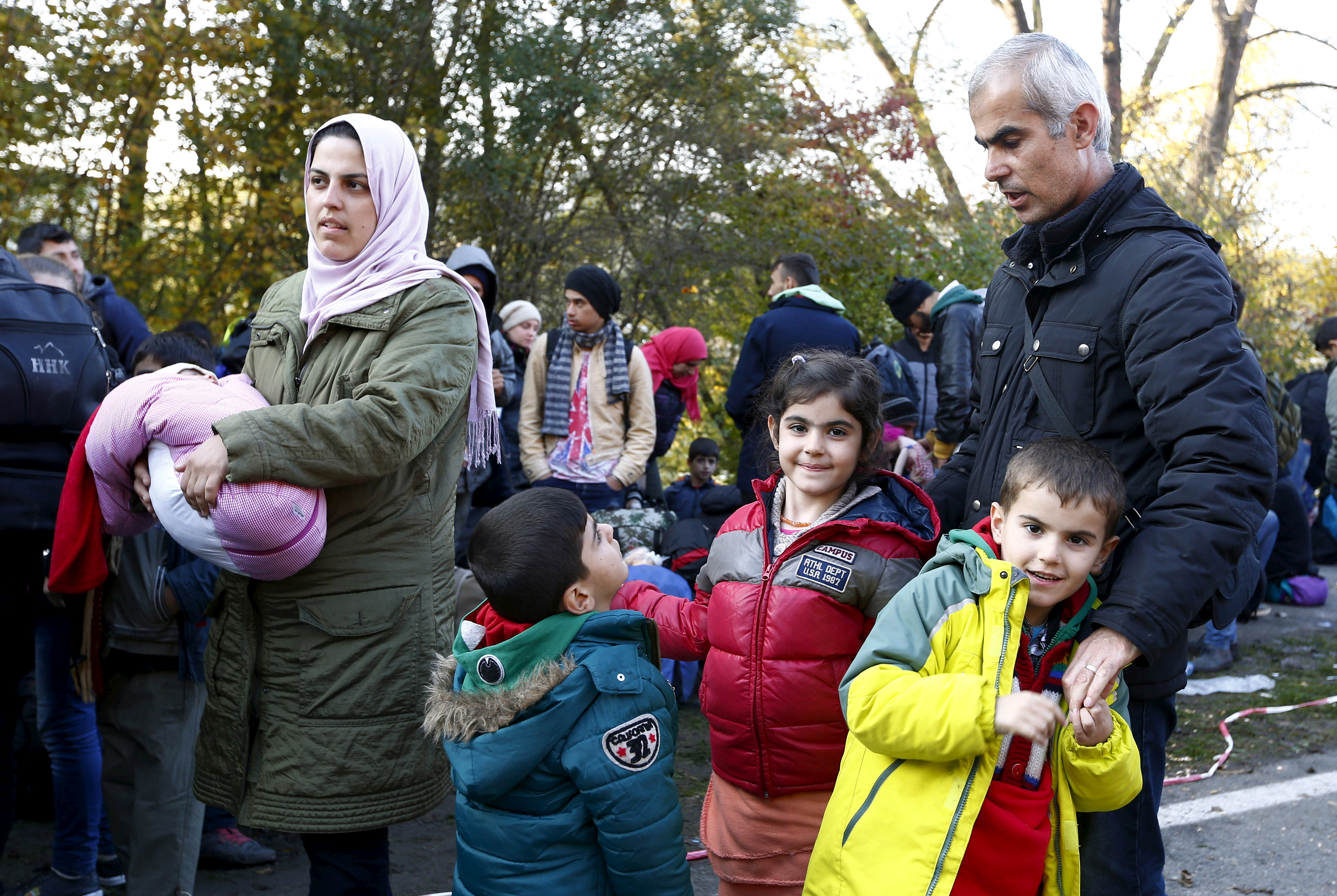 Syrian migrant Zake Khalil (R), his wife Nagwa (L) and their four children Joan (3rd L), Torin (3rd R), Ellen (2nd R) and newborn Hevin arrive at the Austrian-German border in Achleiten near Passau, Germany, October 27, 2015. REUTERS/Michaela Rehle