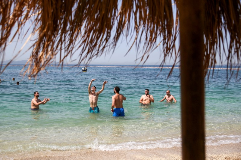 People enjoy the sea near Athens, Greece, during the official reopening of beaches to the public following the easing of measures against the spread of COVID-19, May 8, 2021. REUTERS/Costas Baltas/File Photo