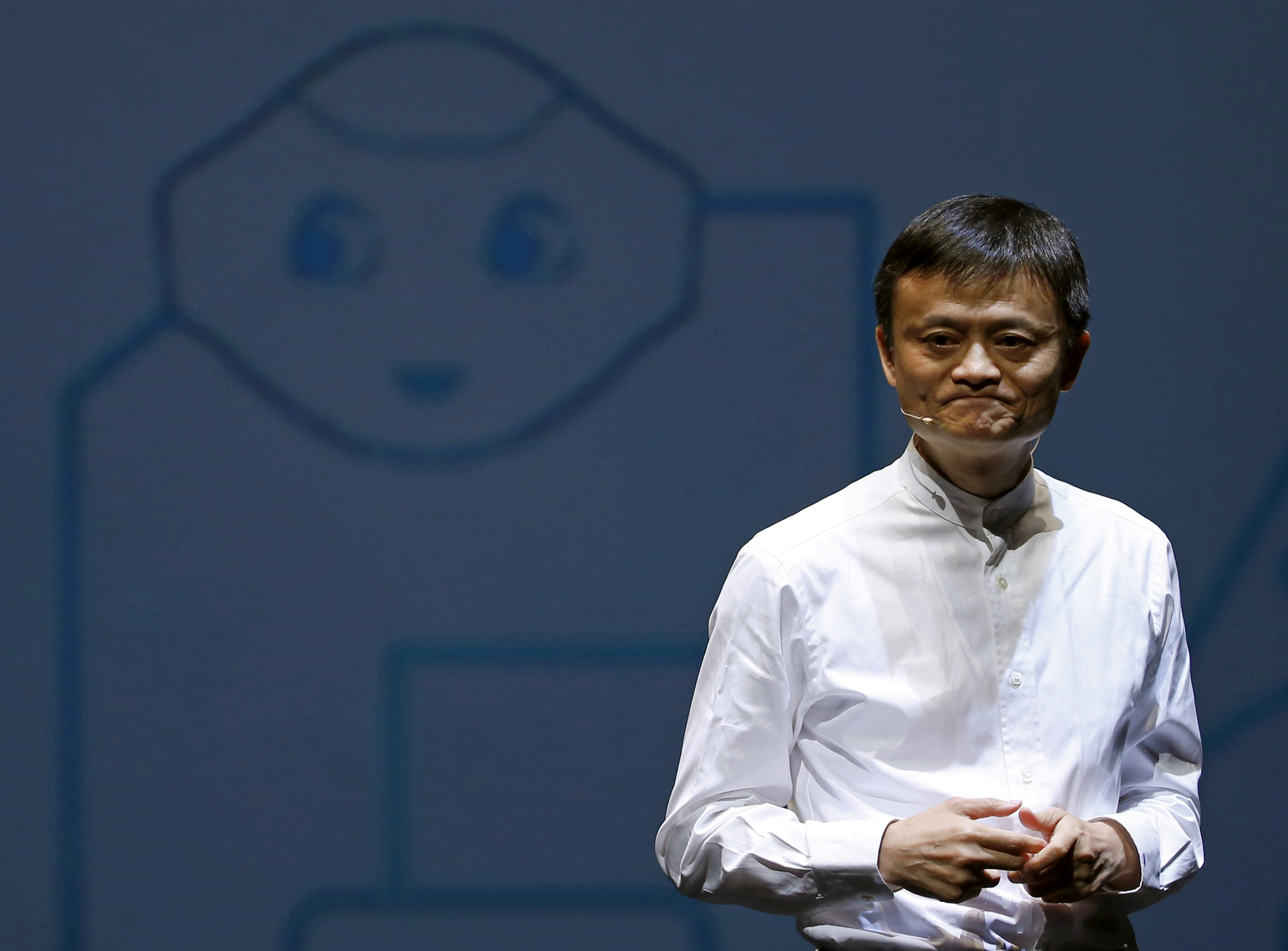 Jack Ma, founder and executive chairman of China's Alibaba Group, speaks in front of a picture of SoftBank's human-like robot named 'pepper' during a news conference in Chiba, Japan, June 18, 2015. REUTERS/Yuya Shino/File Photo