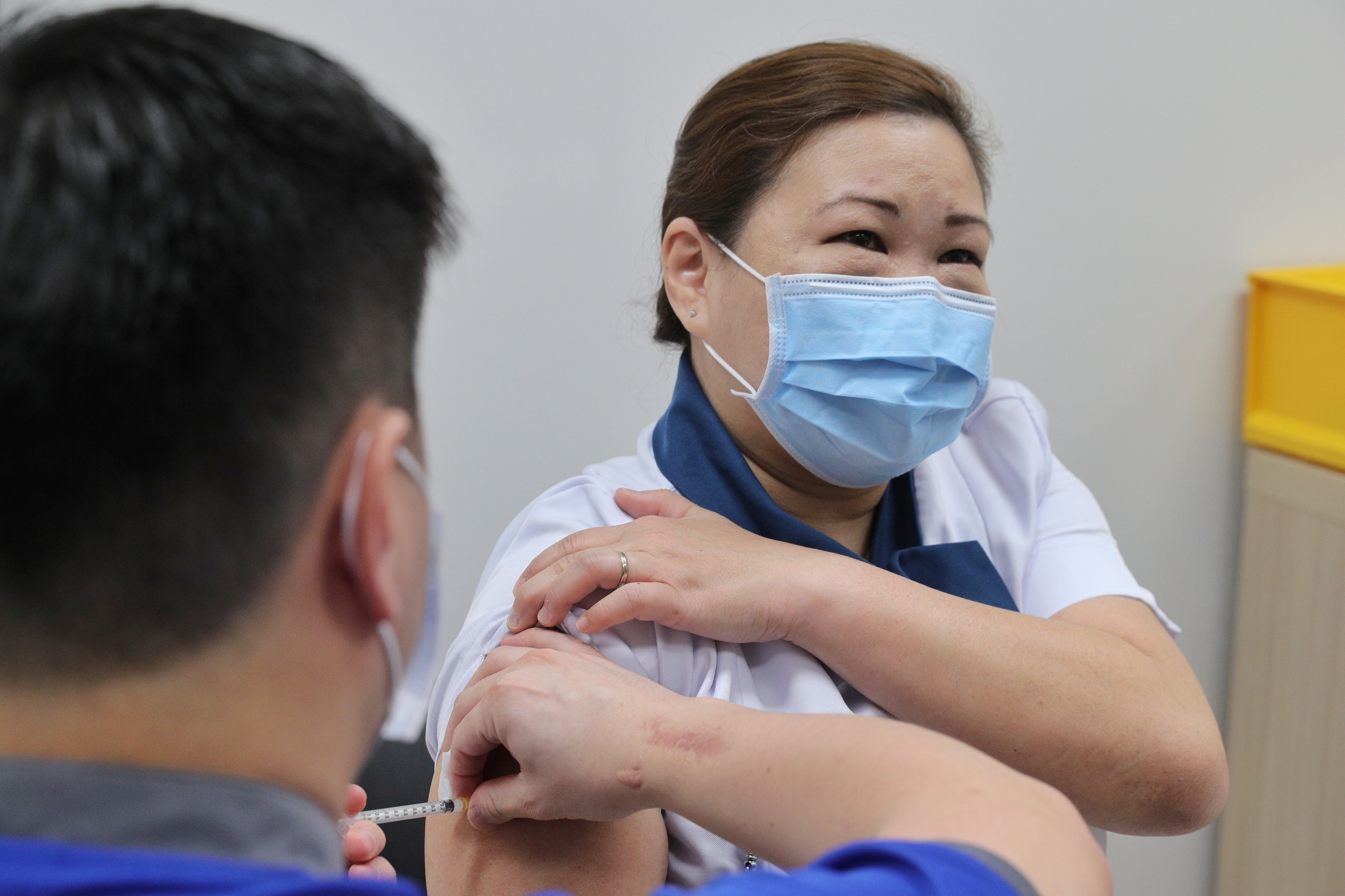 Healthcare worker Sarah Lim receives her coronavirus disease (COVID-19) vaccine at the National Centre for Infectious Diseases (NCID) in Singapore December 30, 2020.  Lee Jia Wen/Ministry of Communications and Information/Handout via REUTERS
