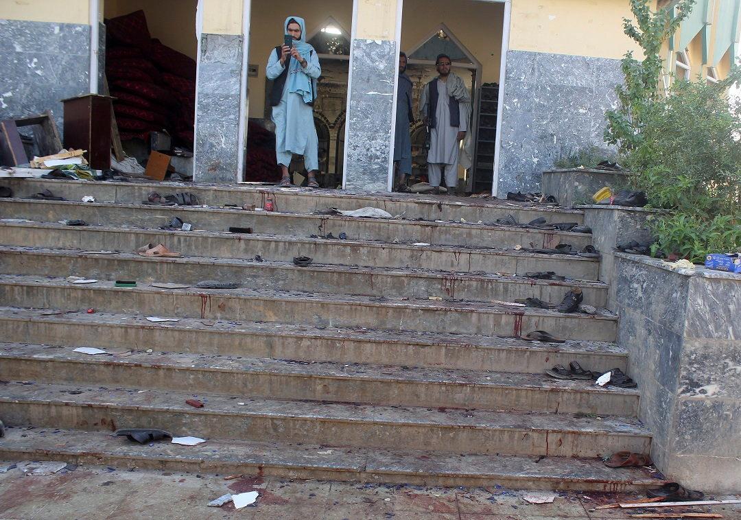 Afghan men stand inside a mosque after a blast, in Kunduz, Afghanistan October 8, 2021. REUTERS/Stringer