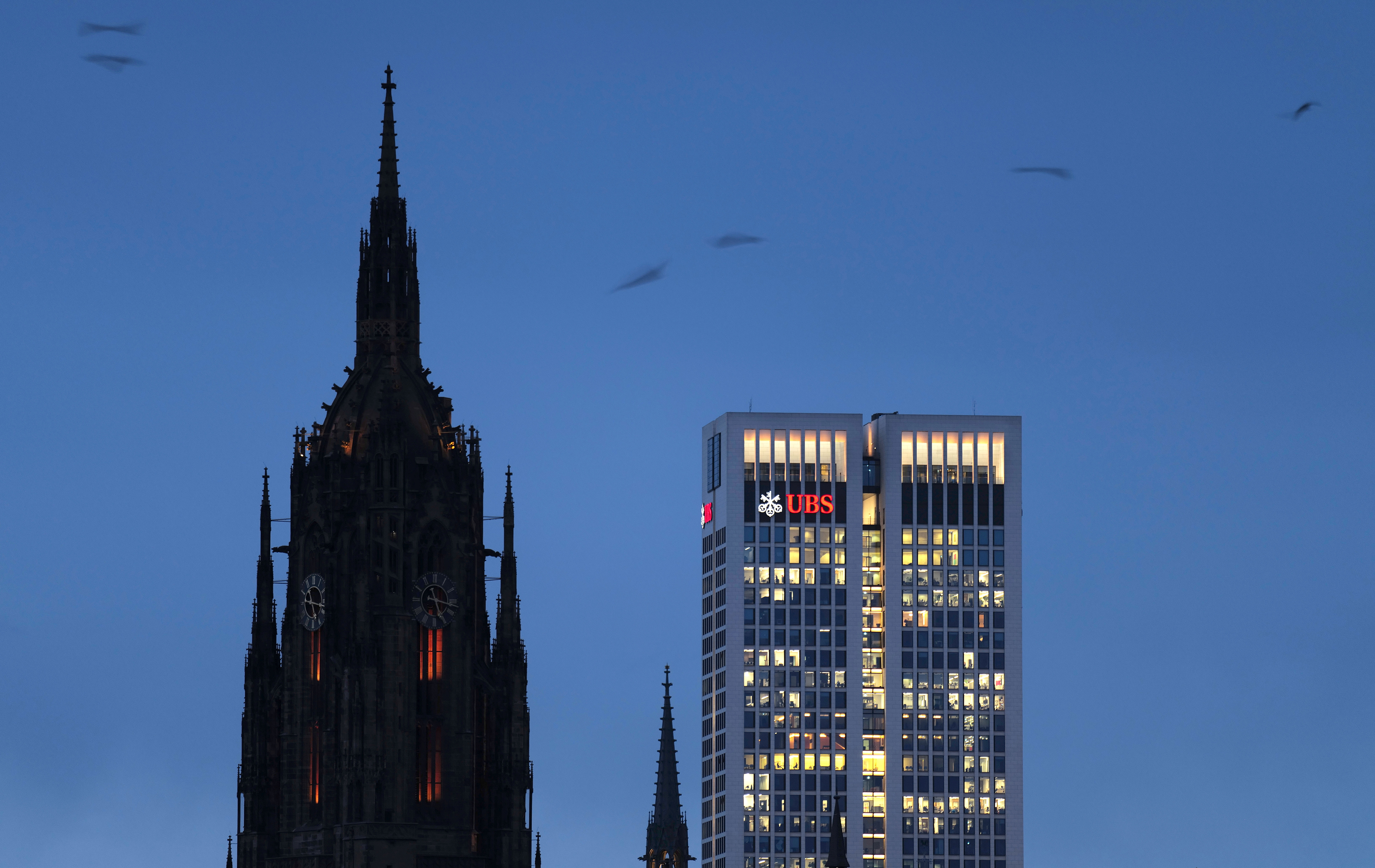 Illuminated offices of the UBS Swiss bank are pictured next to a cathedral during an extended lockdown, as the spread of the coronavirus disease (COVID-19) continues in Frankfurt, Germany, January 21, 2021.  REUTERS/Kai Pfaffenbach - RC2ICL9610BN