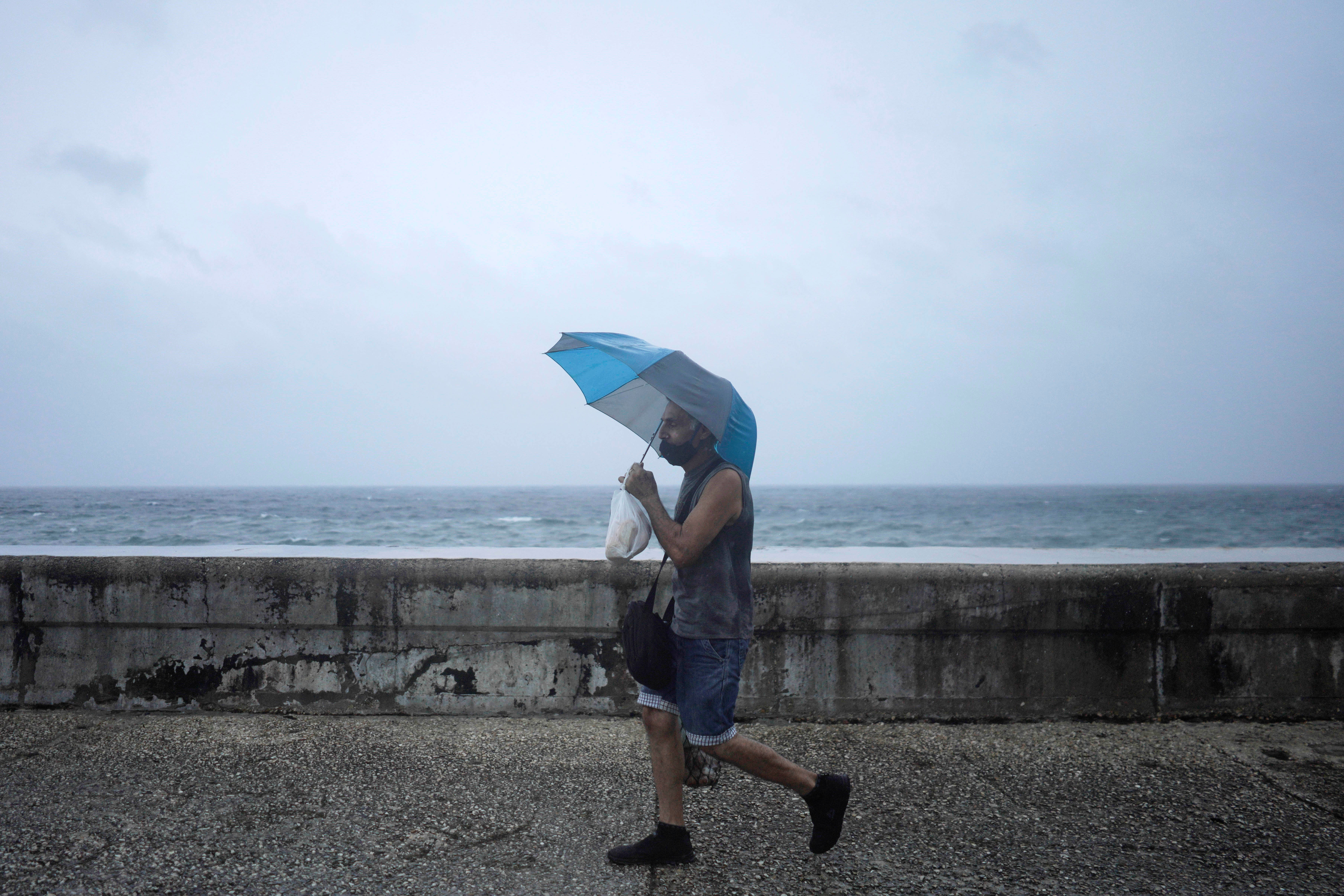 A man protects himself from wind and rain as he walks at the seafront Malecon while Hurricane Ida approaches the island, in Havana, Cuba, August 27, 2021. REUTERS/Alexandre Meneghini