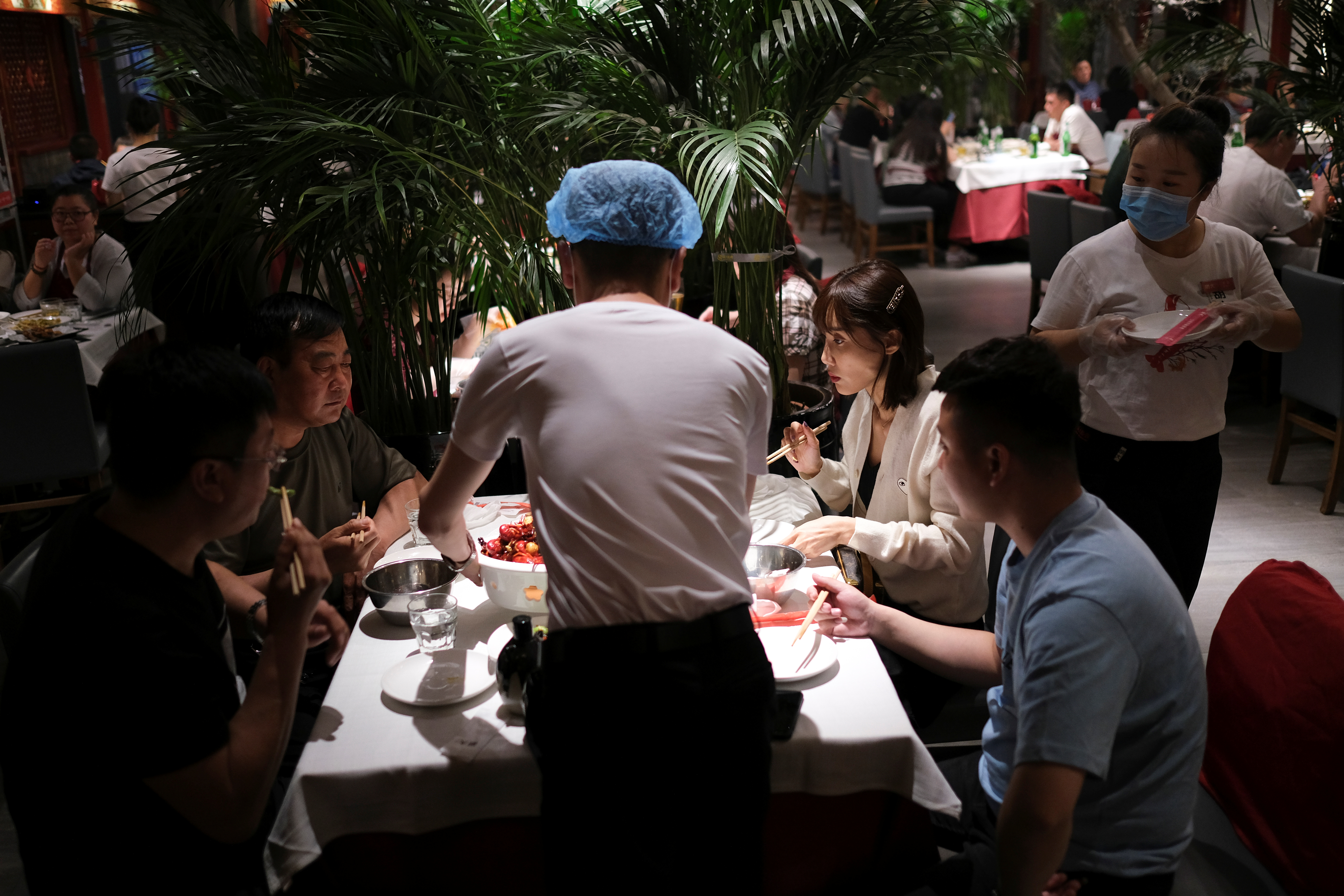 People enjoy their meal at a restaurant, following an outbreak of the coronavirus disease (COVID-19), in Beijing, China May 7, 2020. REUTERS/Carlos Garcia Rawlins