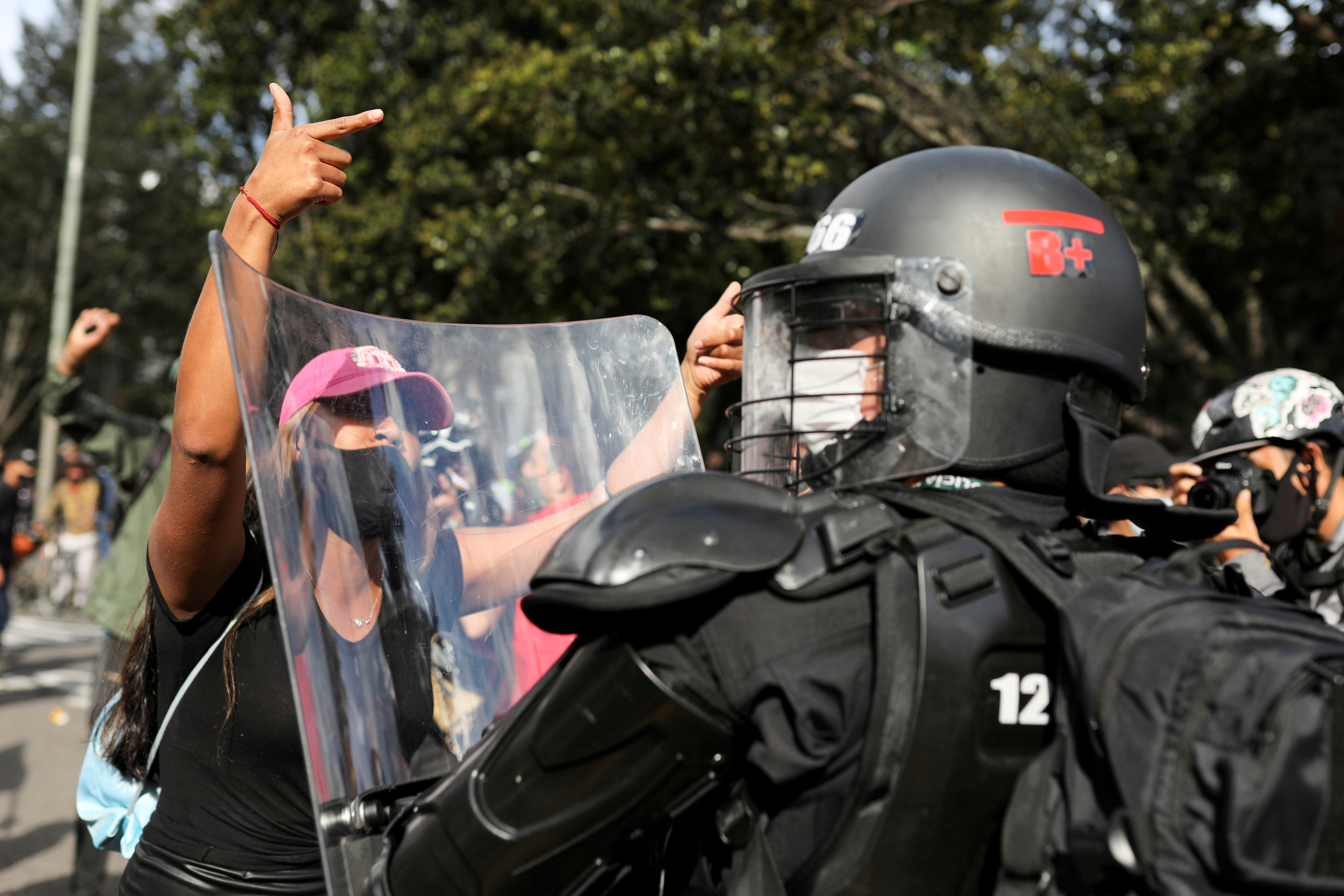 A demonstrator argues with a member of security forces as she takes part in a protest during a national strike, in Bogota, Colombia, November 21, 2020. REUTERS/Luisa Gonzalez/File Photo