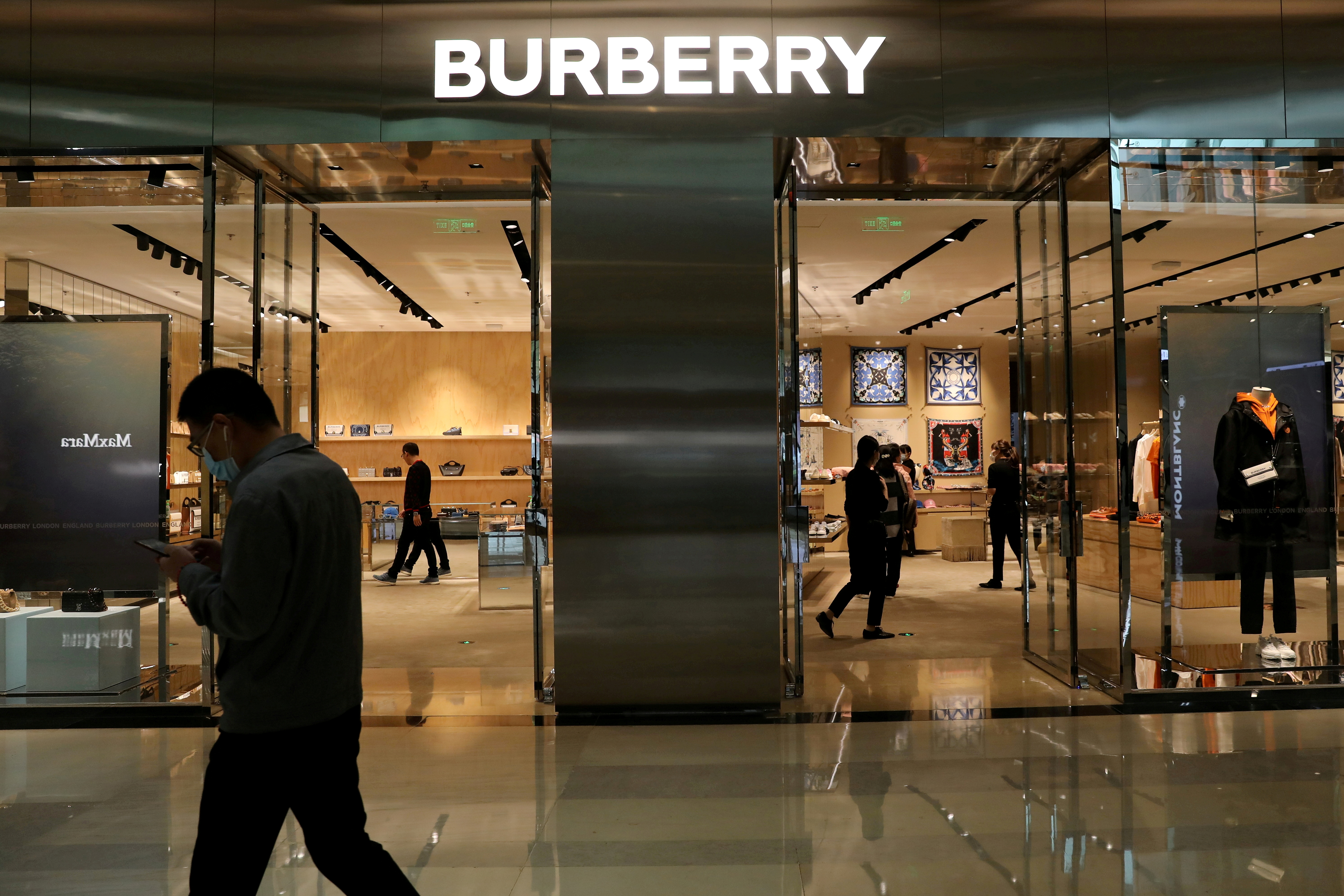 A man walks past a store of luxury brand Burberry at a shopping mall in Beijing, China March 26, 2021. REUTERS/Tingshu Wang
