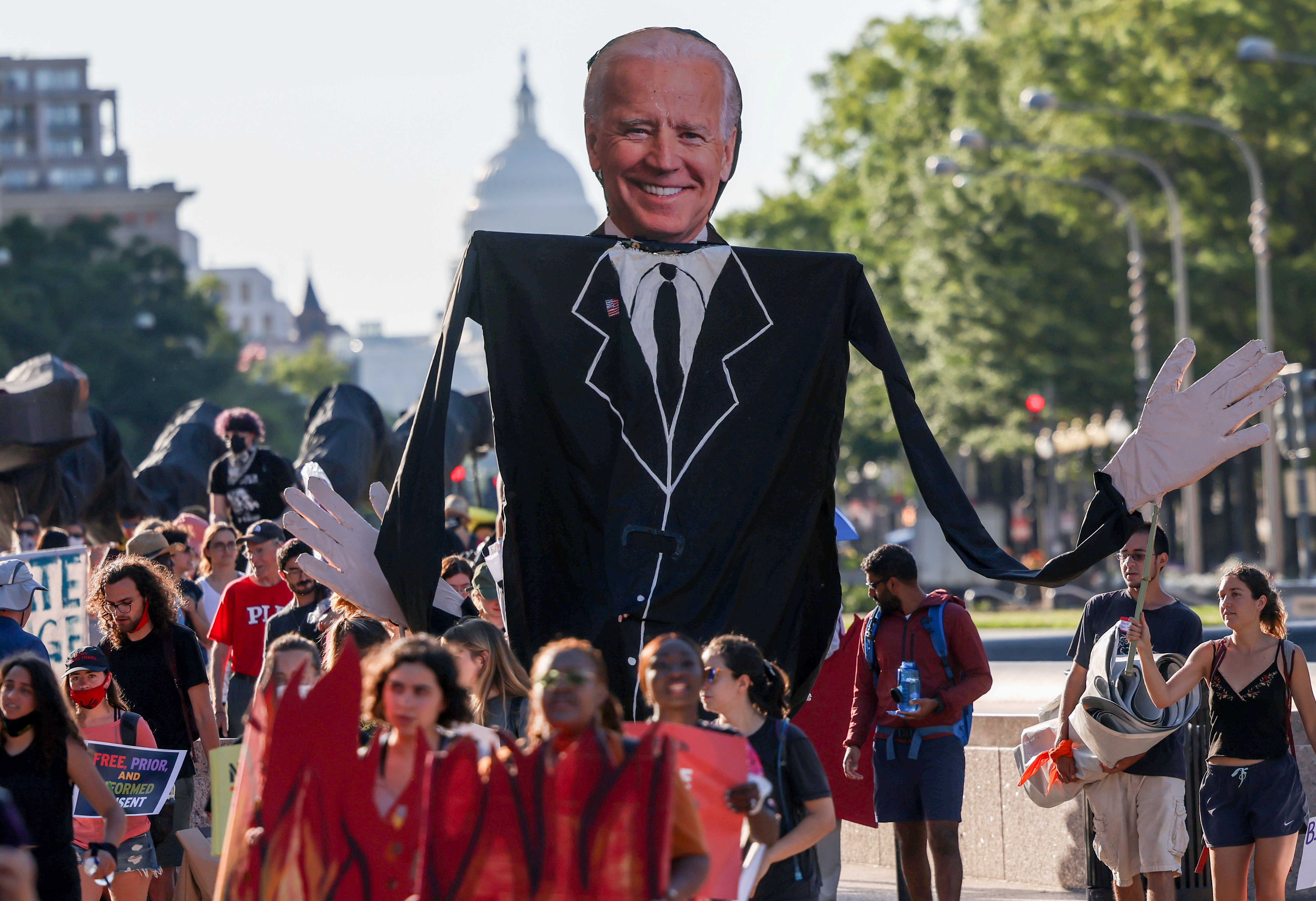 Environmental activists march towards the White House to demand U.S. President Joe Biden stop fossil fuel projects and put climate justice at the heart of his infrastructure plans, in Washington, U.S., June 30, 2021. REUTERS/Evelyn Hockstein