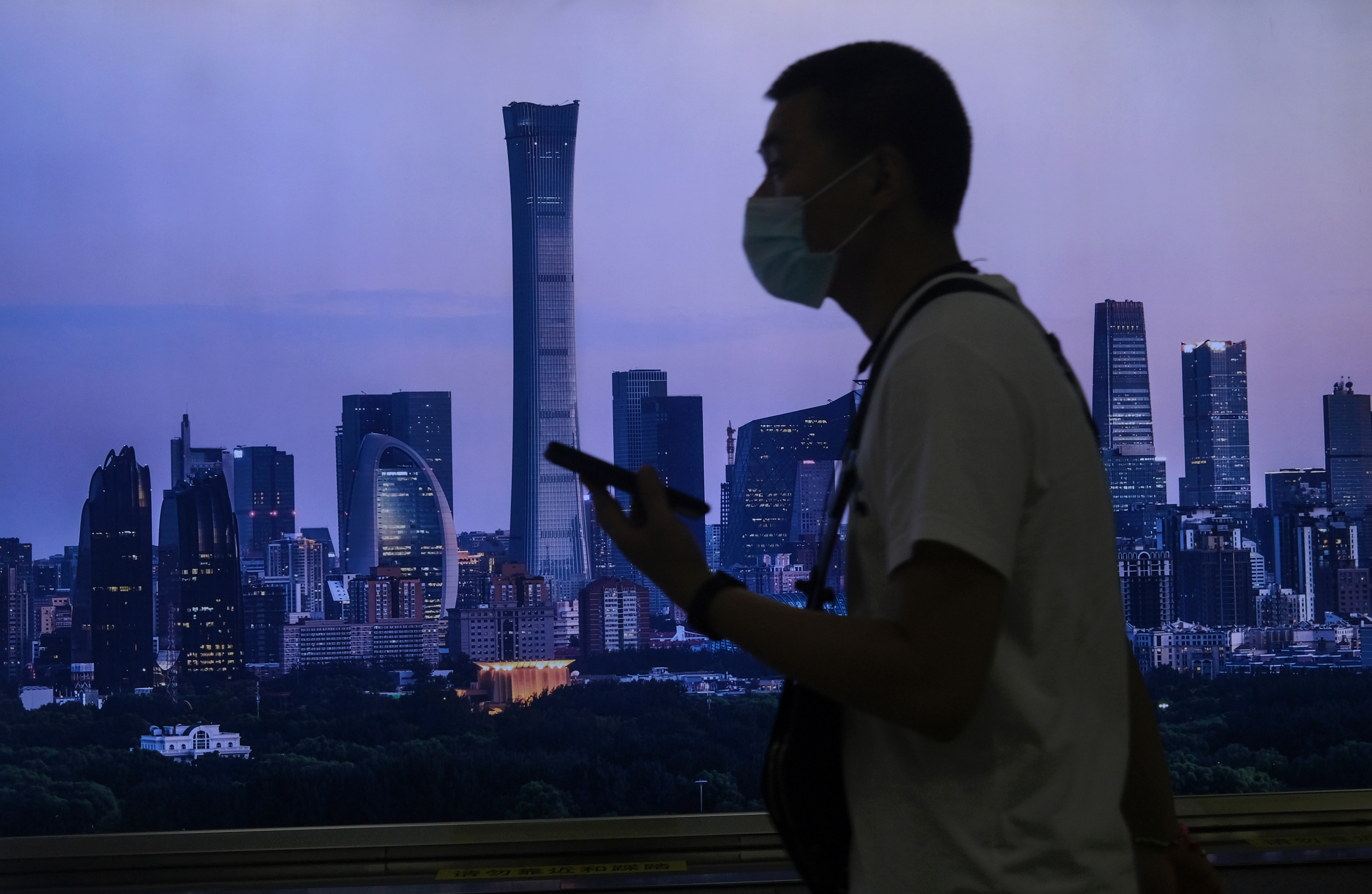 A man wearing a face mask walks past a billboard showing Beijing's city skyline at a subway station, following the coronavirus disease (COVID-19) outbreak, in Beijing, China June 30, 2020. REUTERS/Tingshu Wang/File Photo