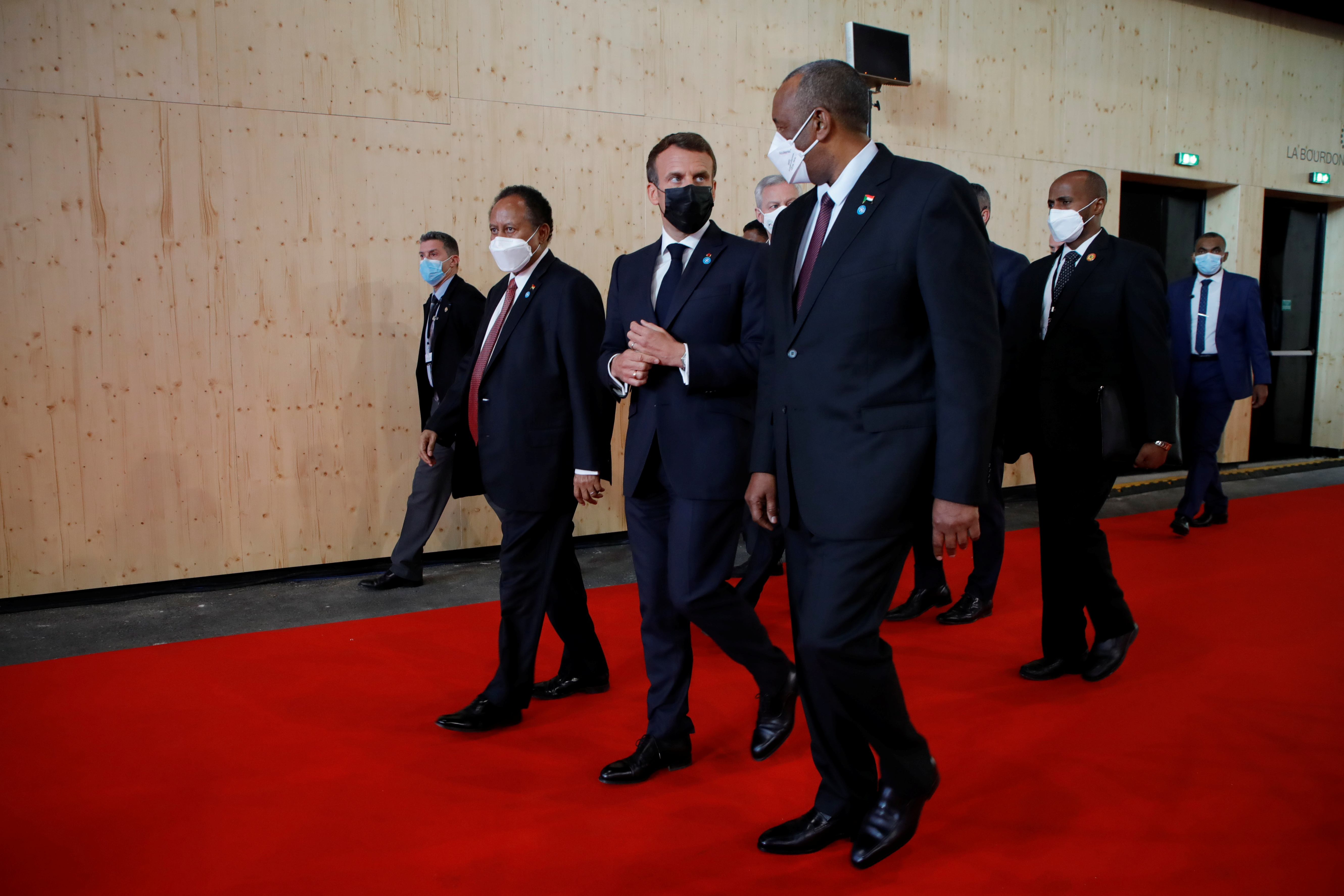 French President Emmanuel Macron walks with Sudan's Sovereign Council Chief General Abdel Fattah al-Burhan and Sudan's Prime Minister Abdalla Hamdok before a joint news conference during the International Conference in support of Sudan at the Temporary Grand Palais in Paris, France, May 17, 2021. REUTERS/Sarah Meyssonnier/Pool