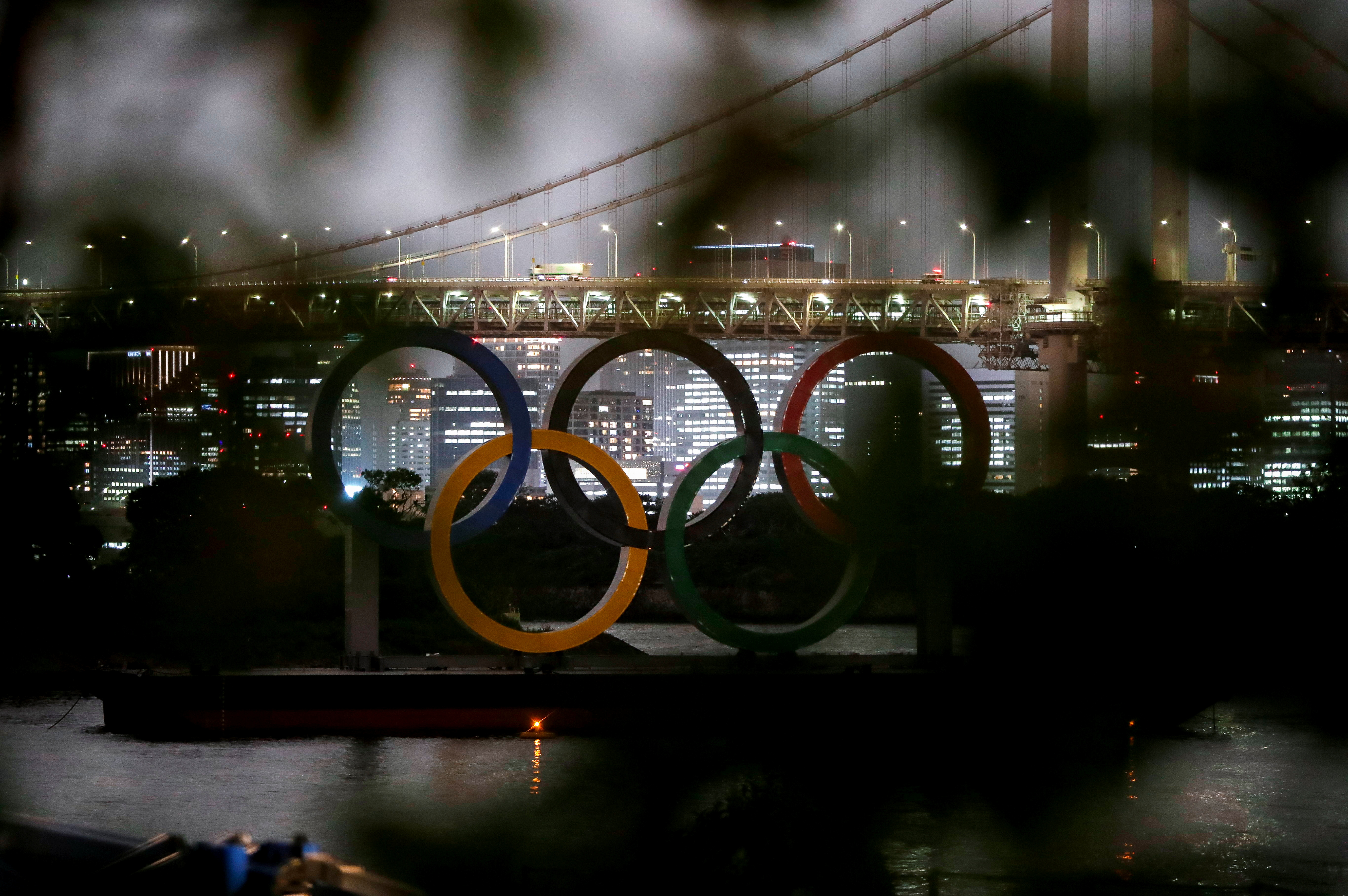The giant Olympic rings are seen through a tree at the waterfront area of Odaiba Marine Park, 50 days before the opening ceremony of the 2020 Tokyo Olympic Games, that have been postponed to 2021 due to the coronavirus disease (COVID-19) outbreak, in Tokyo, Japan June 3, 2021.  REUTERS/Issei Kato