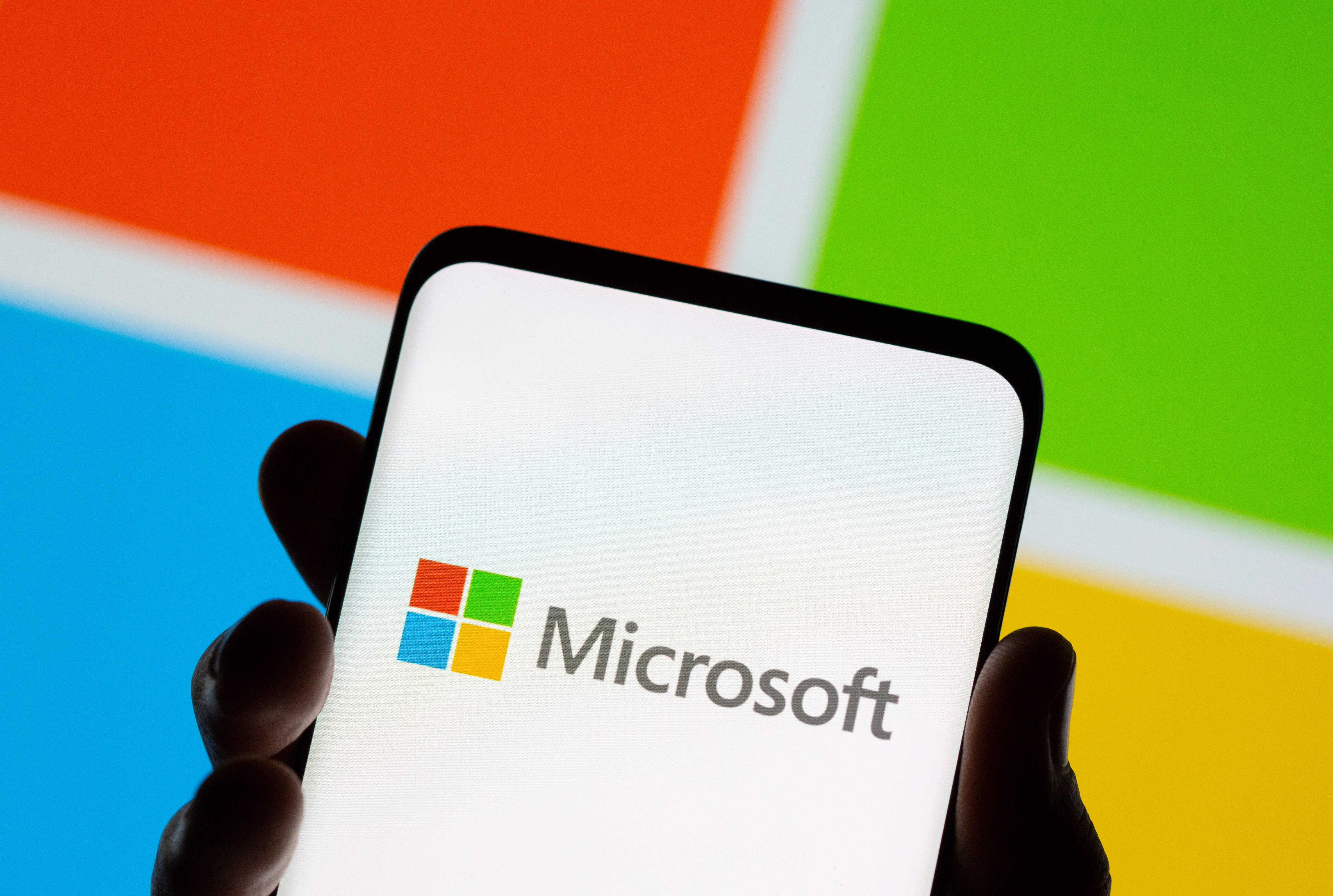 Smartphone is seen in front of Microsoft logo displayed in this illustration taken, July 26, 2021. REUTERS/Dado Ruvic/Illustration