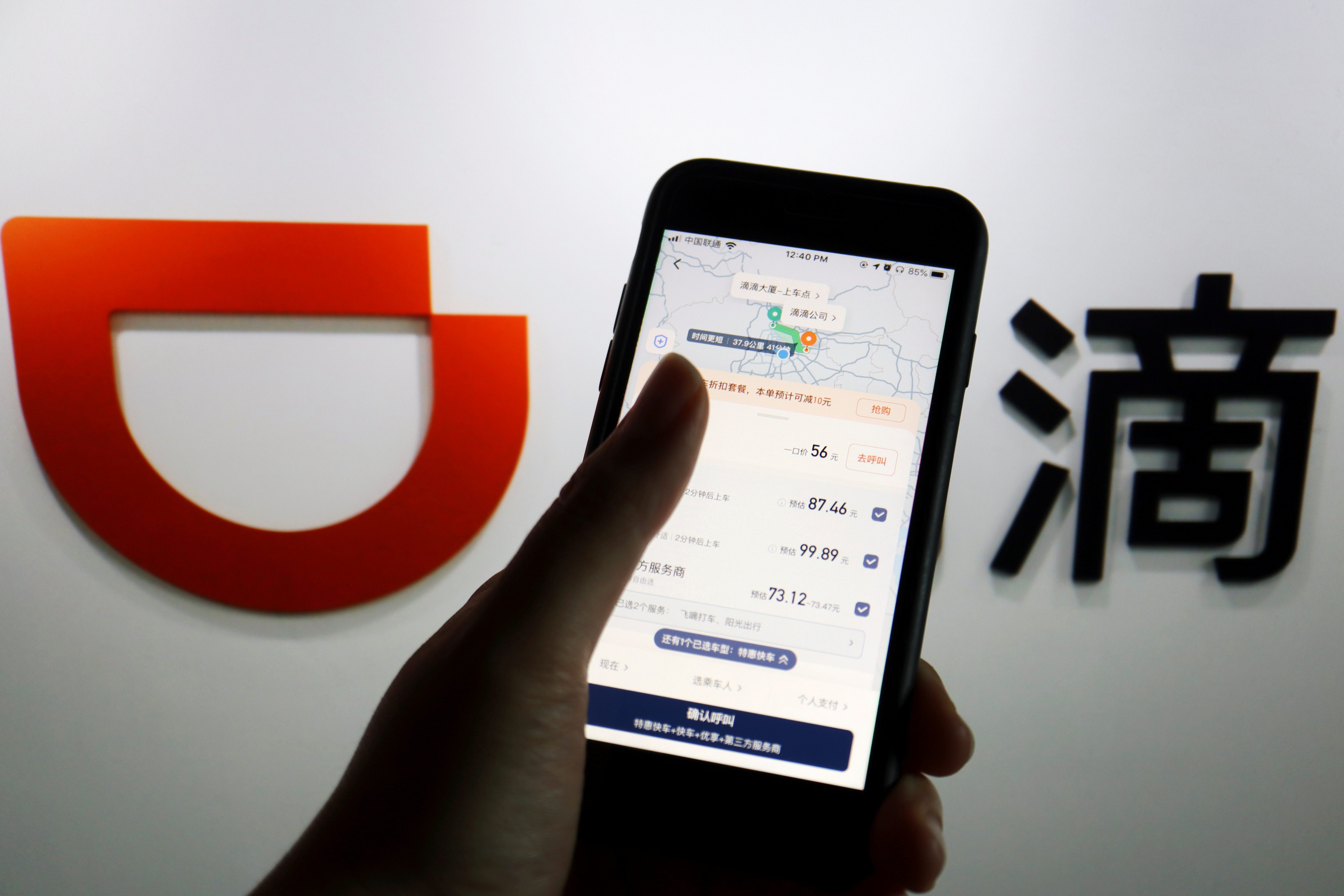 The app of Chinese ride-hailing giant Didi is seen on a mobile phone in front of the company logo displayed in this illustration picture taken July 1, 2021. REUTERS/Florence Lo/Illustration/File Photo