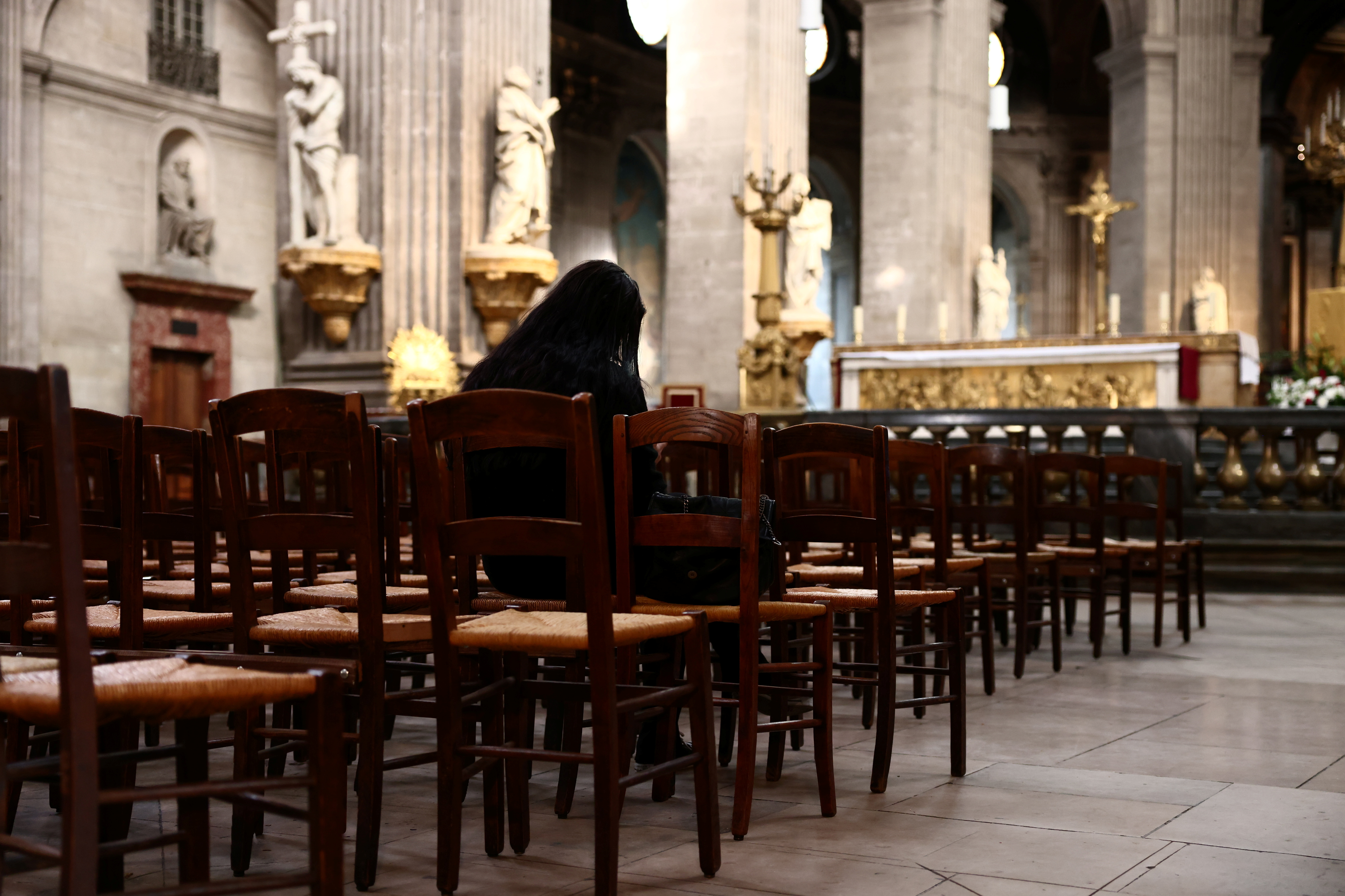 A woman prays inside the Saint-Sulpice church in Paris, France, October 4, 2021. Picture taken October 4, 2021. REUTERS/Sarah Meyssonnier